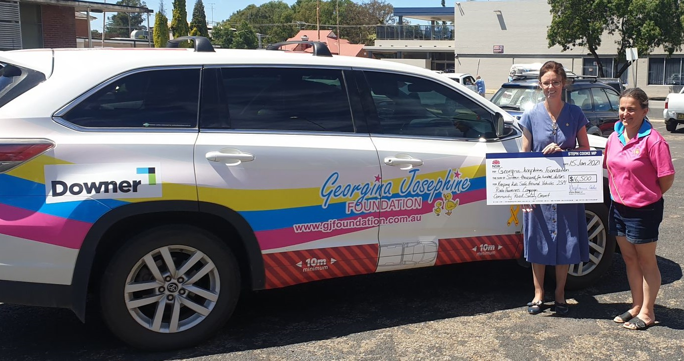 Steph Cooke and Emma Cockburn stand beside a brightly decorated car with the Georgina Josephine Foundation logo on it.