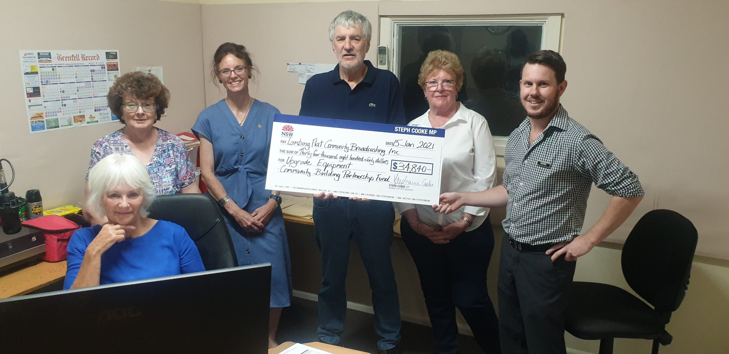Steph Cooke with Young Community Radio volunteers Maureen Perkins, Betty Smithers, Tony Gentle, Bonnie Dudman and David Munnerly. They hold a large cheque in a small office.