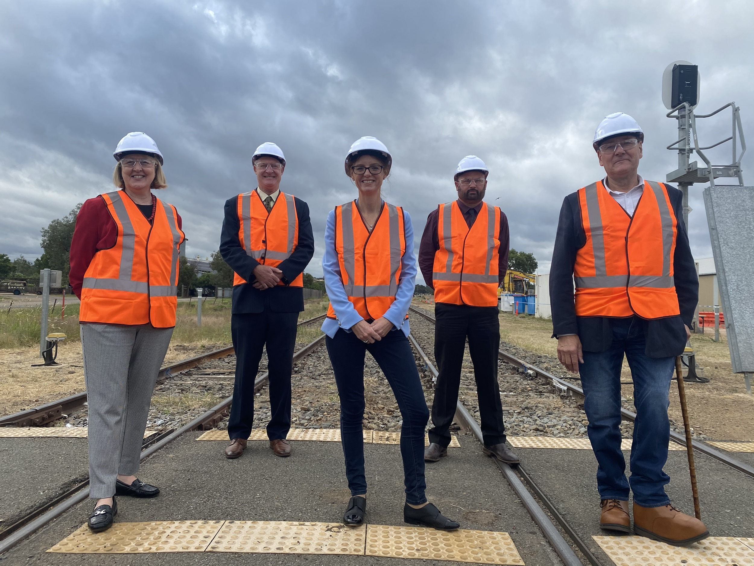 Sam Knight, Luke Taberner, Steph Cooke MP, Cole Davis Neil Smith stand on railway lines, wearing high vis vests and hard hats.