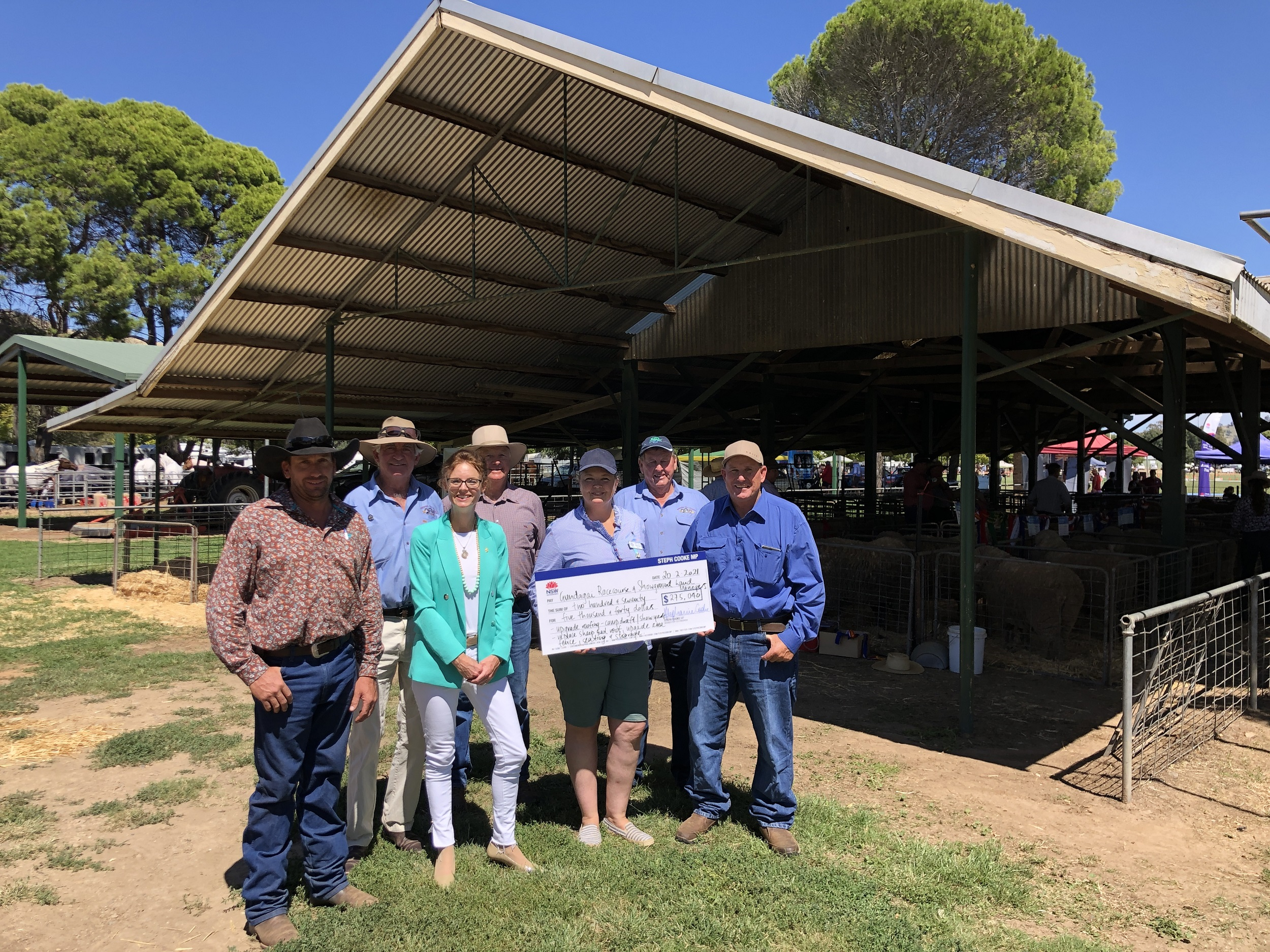 Steph Cooke stands with a group of people holding a large cheque in front of a livestock area.