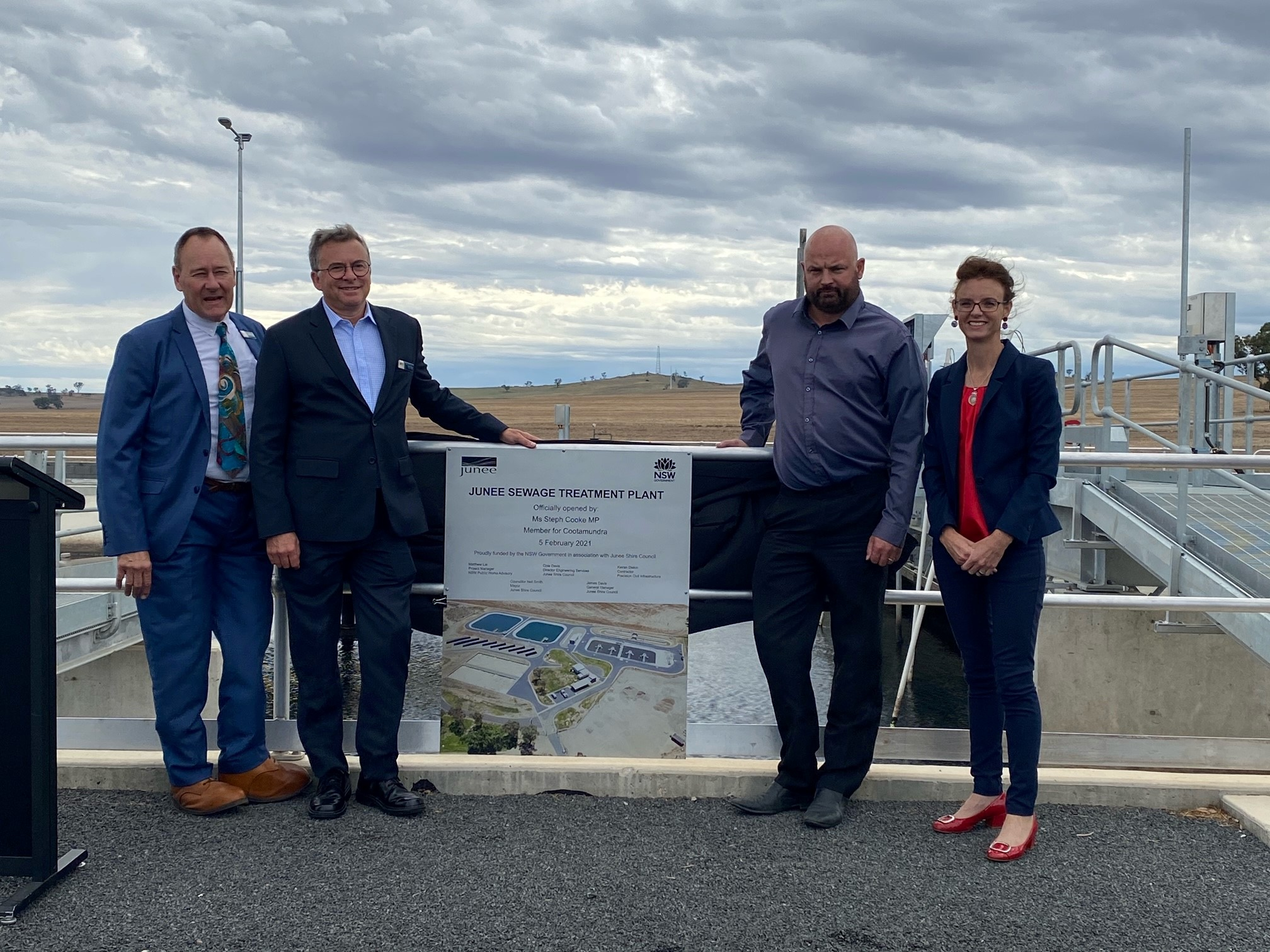 Cr Neil Smith, James Davis, Cole Davis and Steph Cooke MP stand next to a sign that reads 'Junee Sewerage Treatment Plant' and lean against a railing. Behind them is a pool of sewerage water.