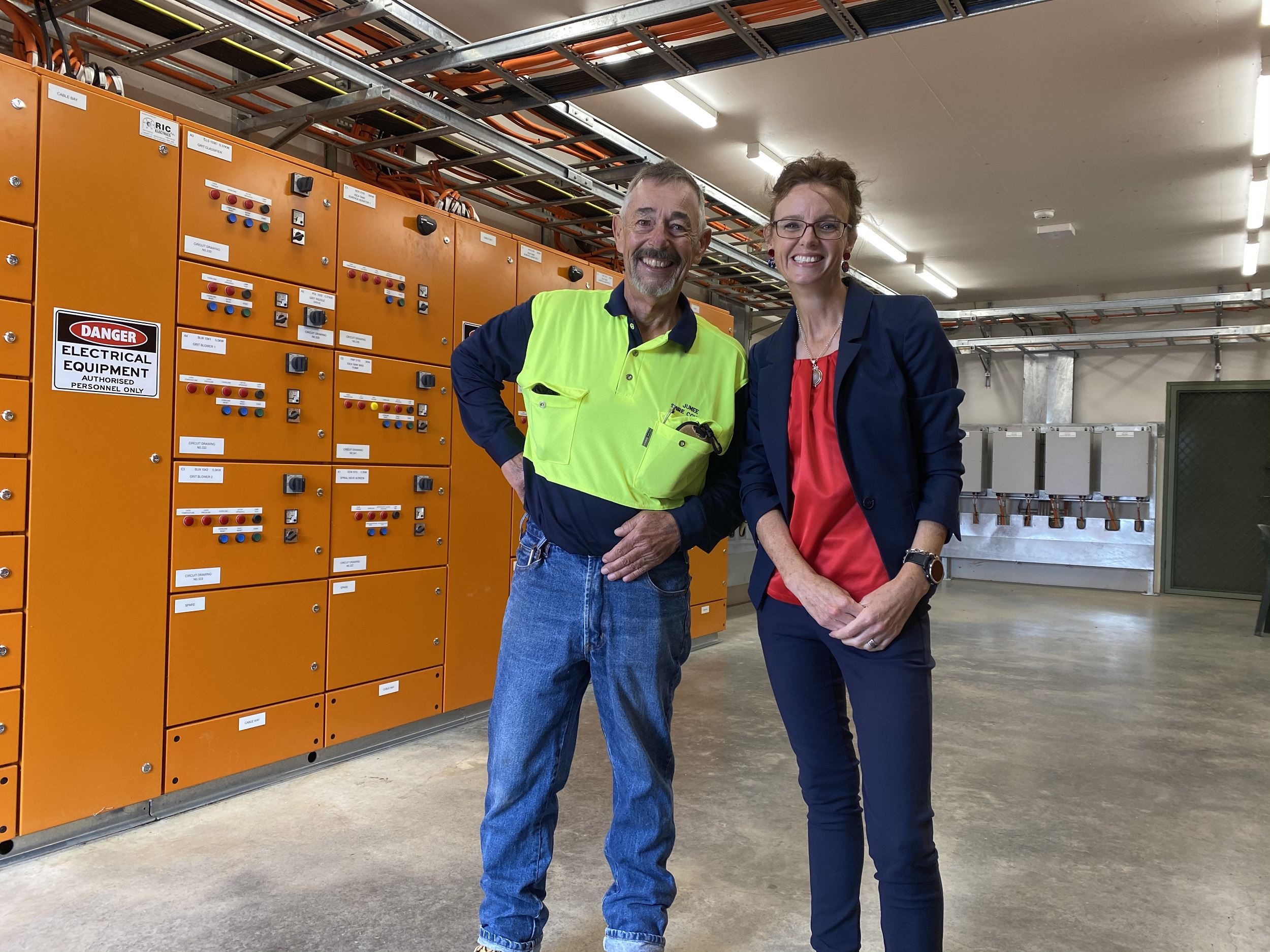 Michael Summerell and Steph Cooke stand in front of orange control panels and stand on a polished concrete floor.