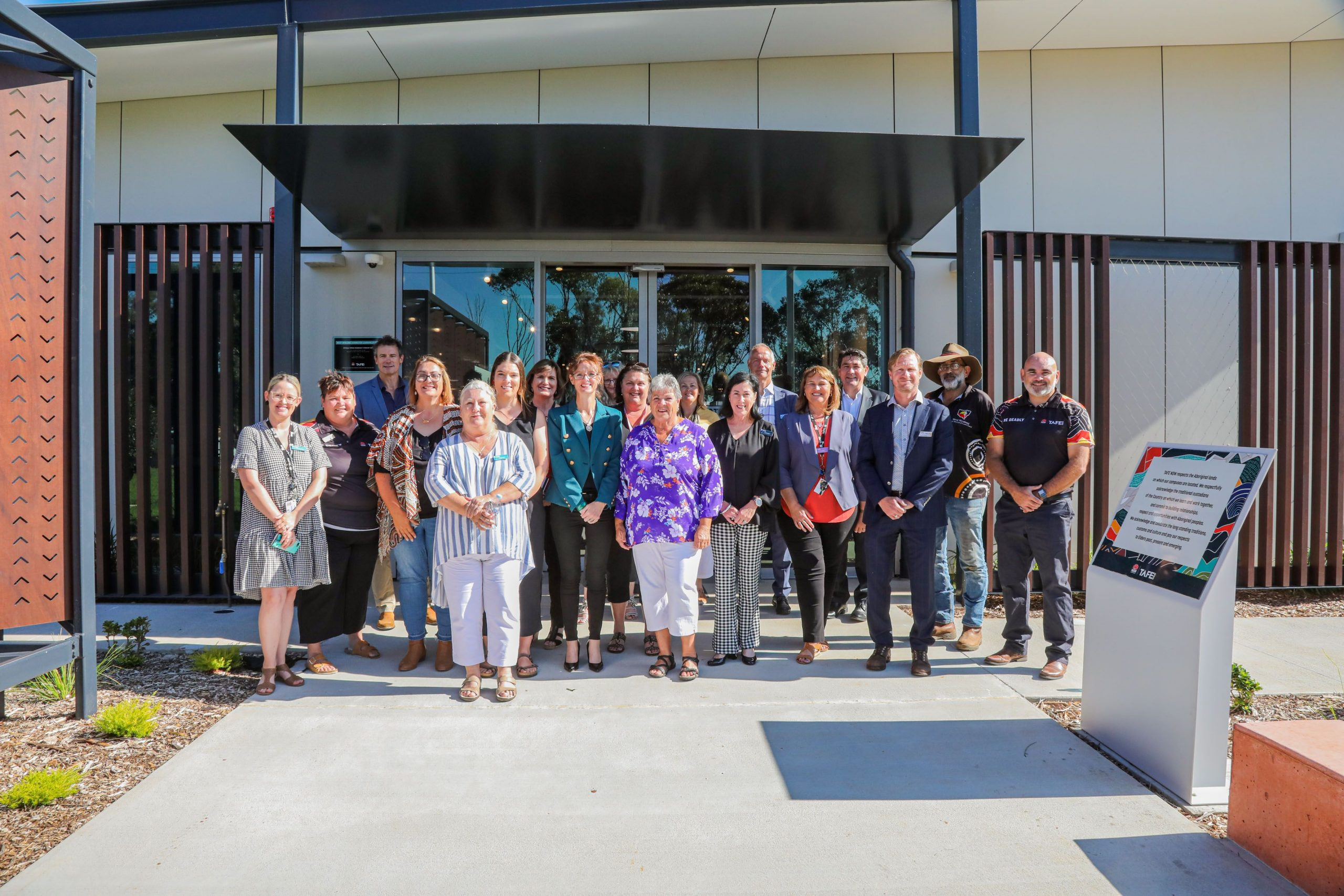 Steph Cooke and Minister Lee stand in a group of TAFE staff in front of a new building.