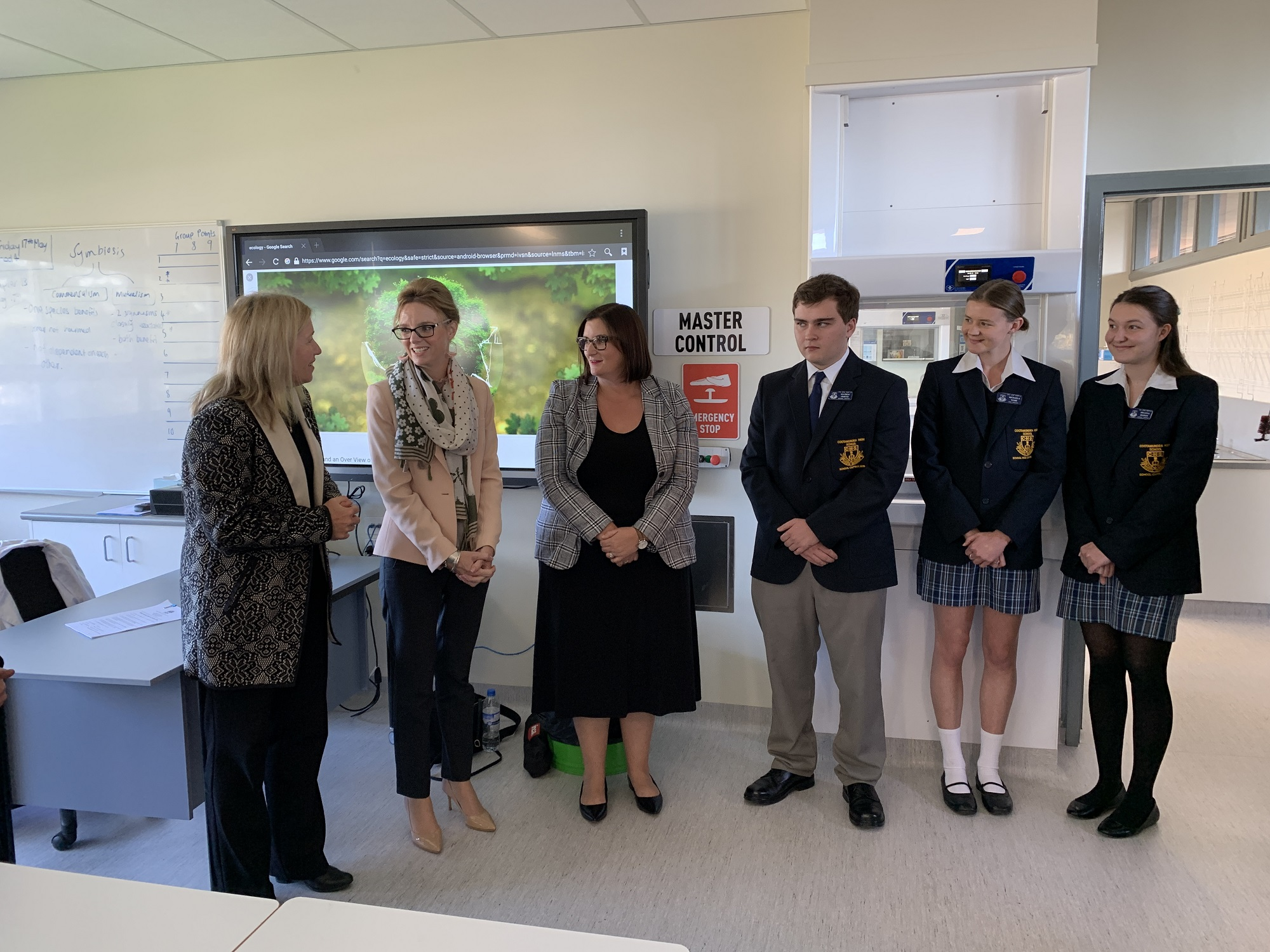 Steph Cooke MP and Minister Sarah Mitchell stand in science labs with three high school students in blazers and a teacher.