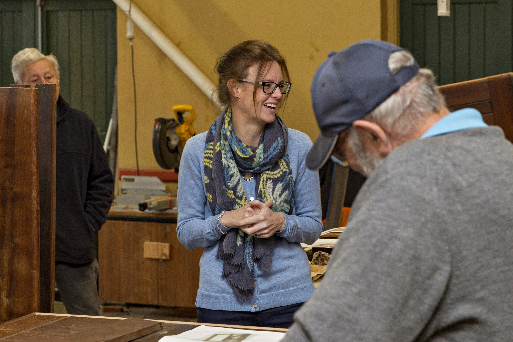 Steph Cooke looks to the right and laughs. In the foreground is a grey-haired man with a cap on who faces away from the camera.