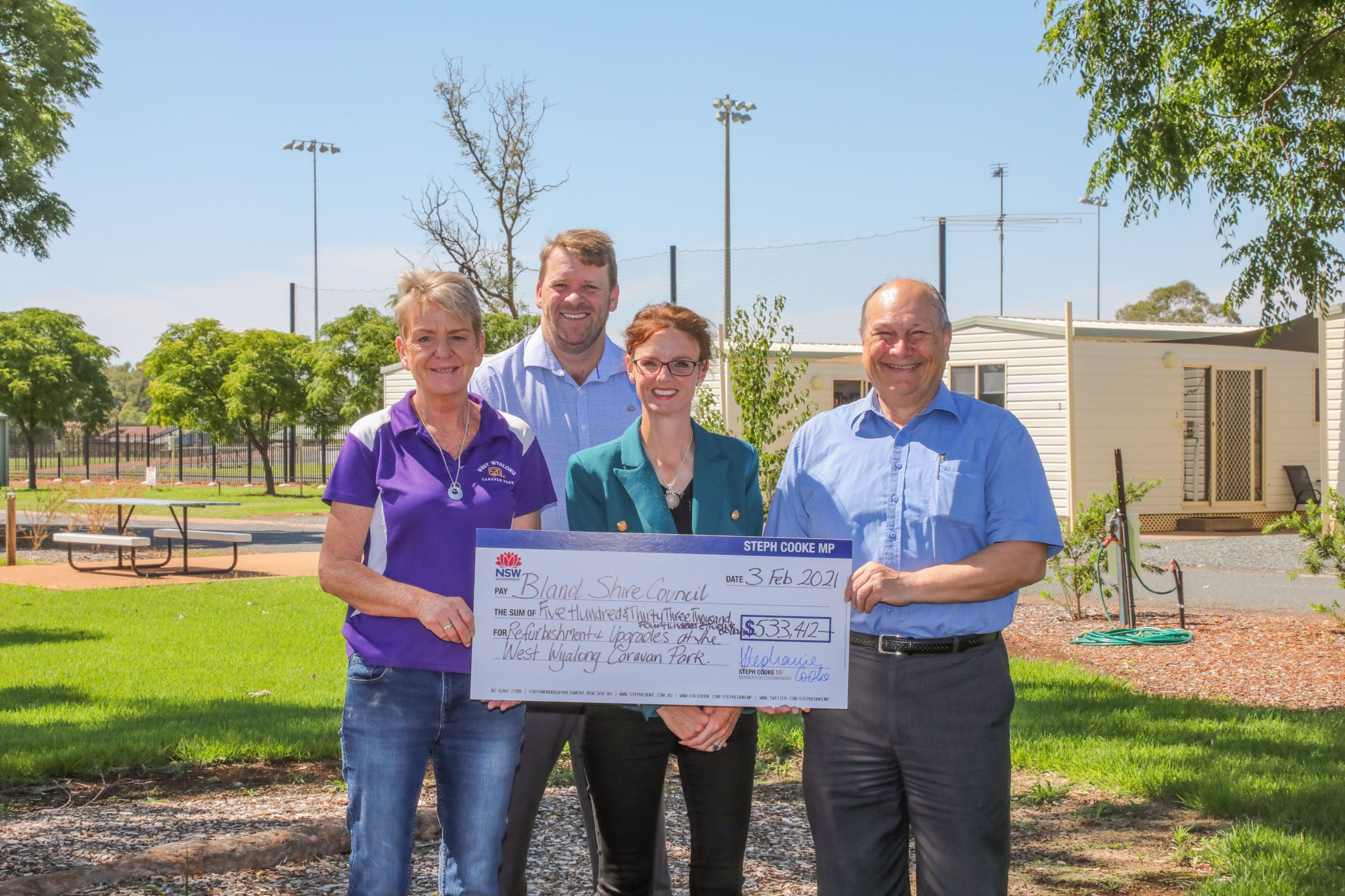 Steph Cooke stands with a woman and two men. They hold a large cheque and cabins are behind them.
