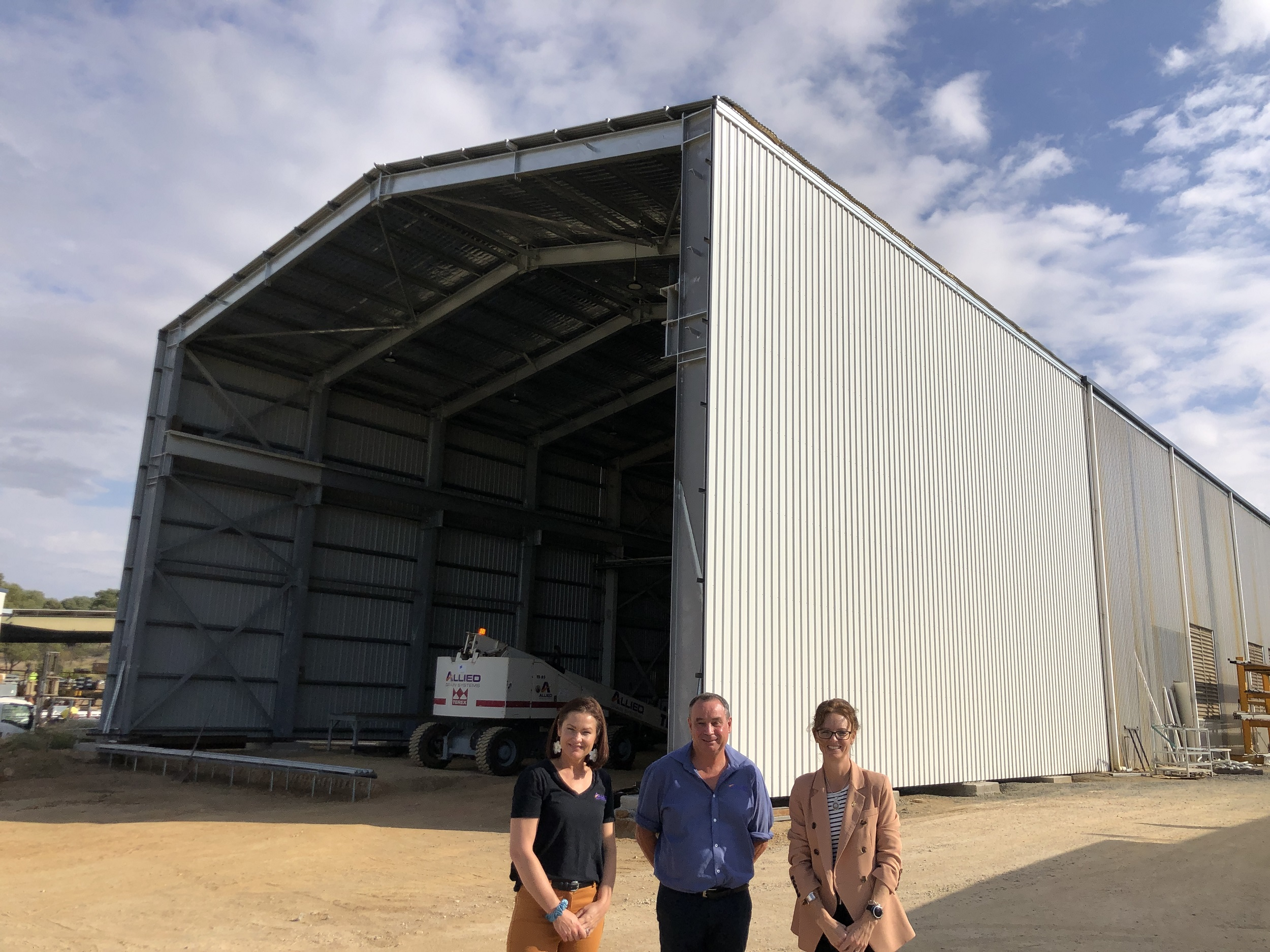 Sheree Gibson and John White and Steph Cooke stand in front of a very large shed, inside is apiece of machinery with 'allied' written on it.