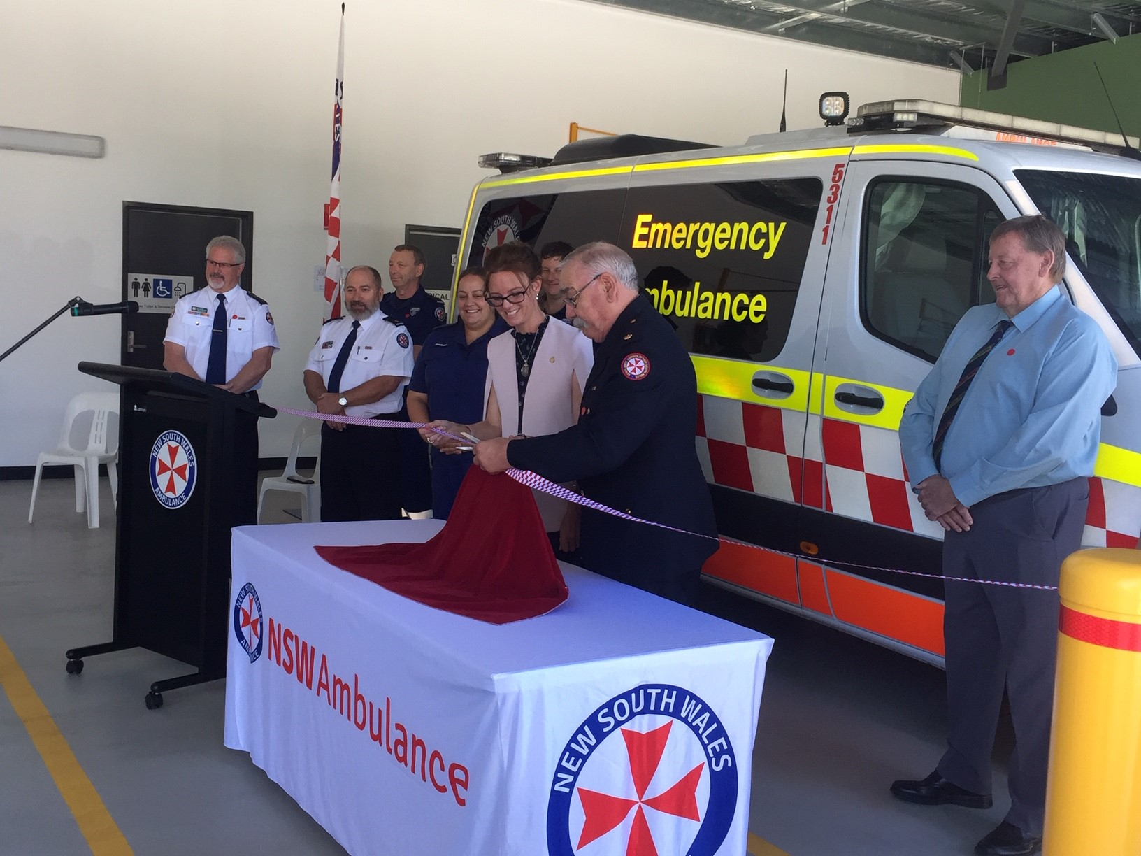 Steph Cooke stands with NSW Ambulance staff and cuts a chequered ribbon.