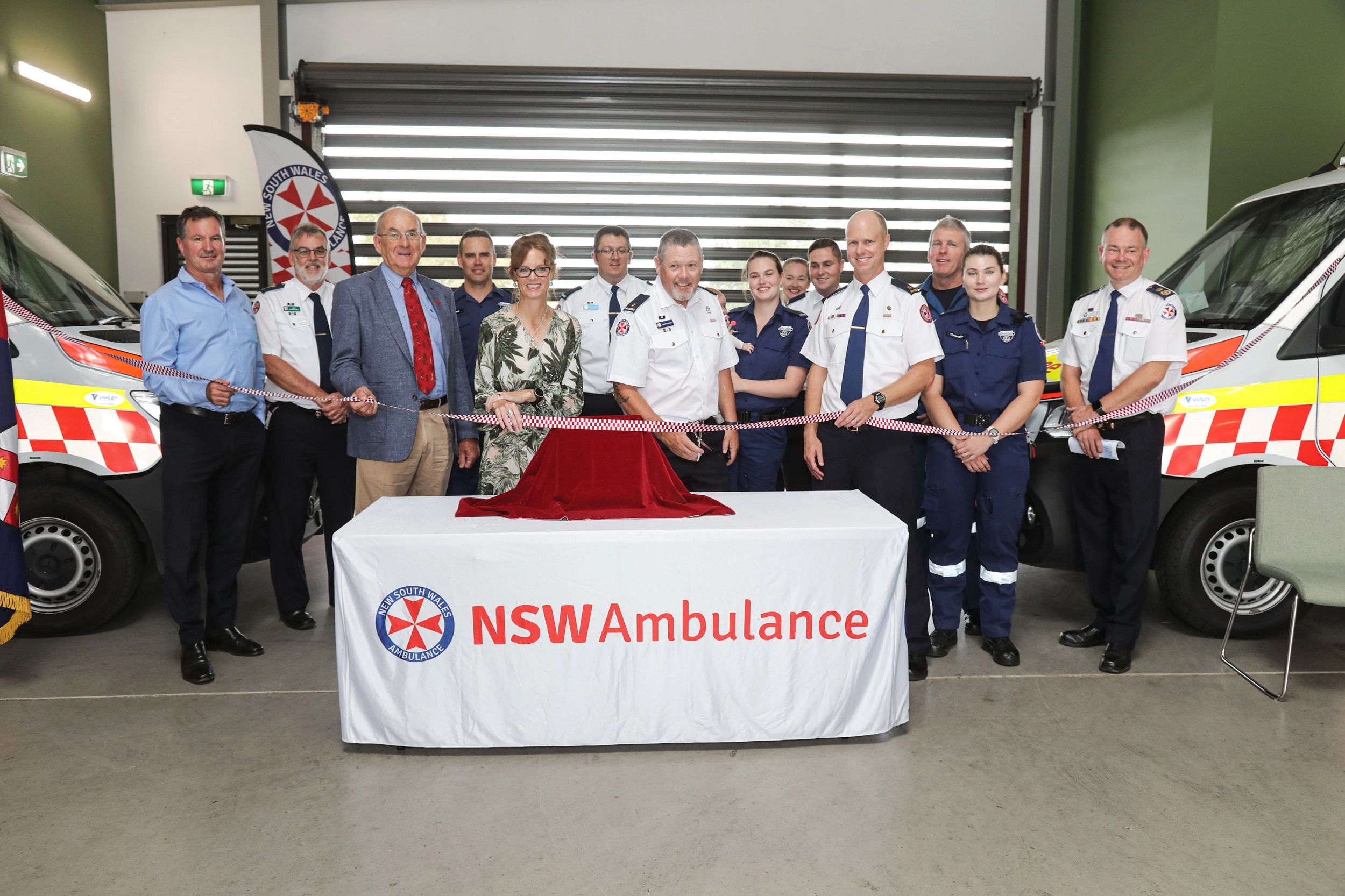 A group of paramedics and Steph Cooke cut a red and white ribbon.