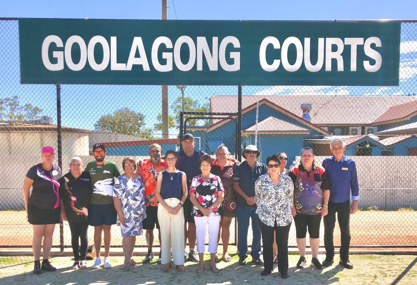 Steph Cooke stands with members of the community and the Goolagong family in front of a fence and sign that reads Goolagong Courts.
