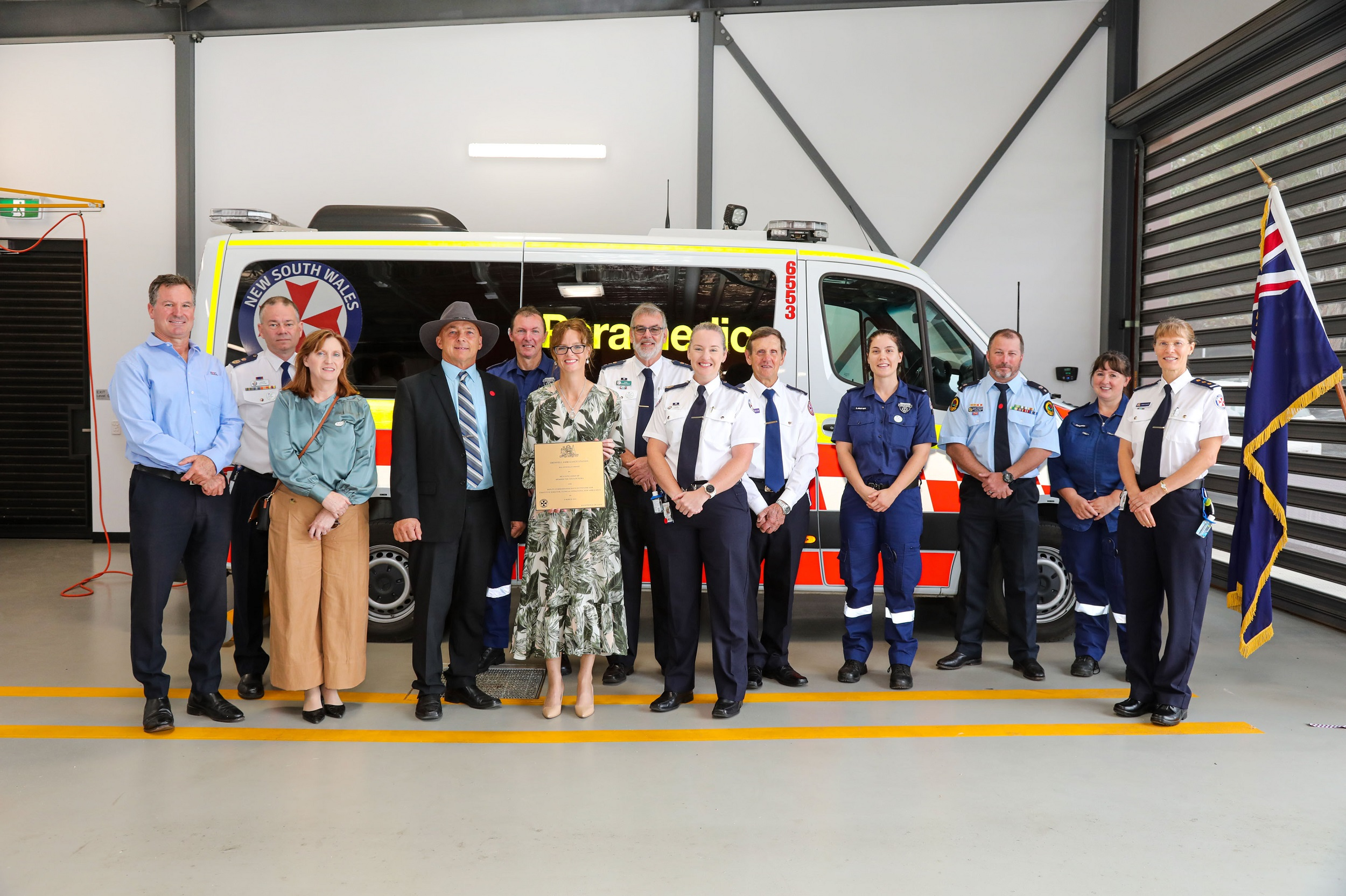 David Hines, David Dutton, Annabelle Dunlop, Weddin Shire Mayor Mark Liebich, paramedic Andrew, Steph Cooke MP, John Stonestreet, Clare Lorenzen, Rev. Richard, Lauren, Barry, and Penelope Child stand in front of an ambulance and smile at the camera.