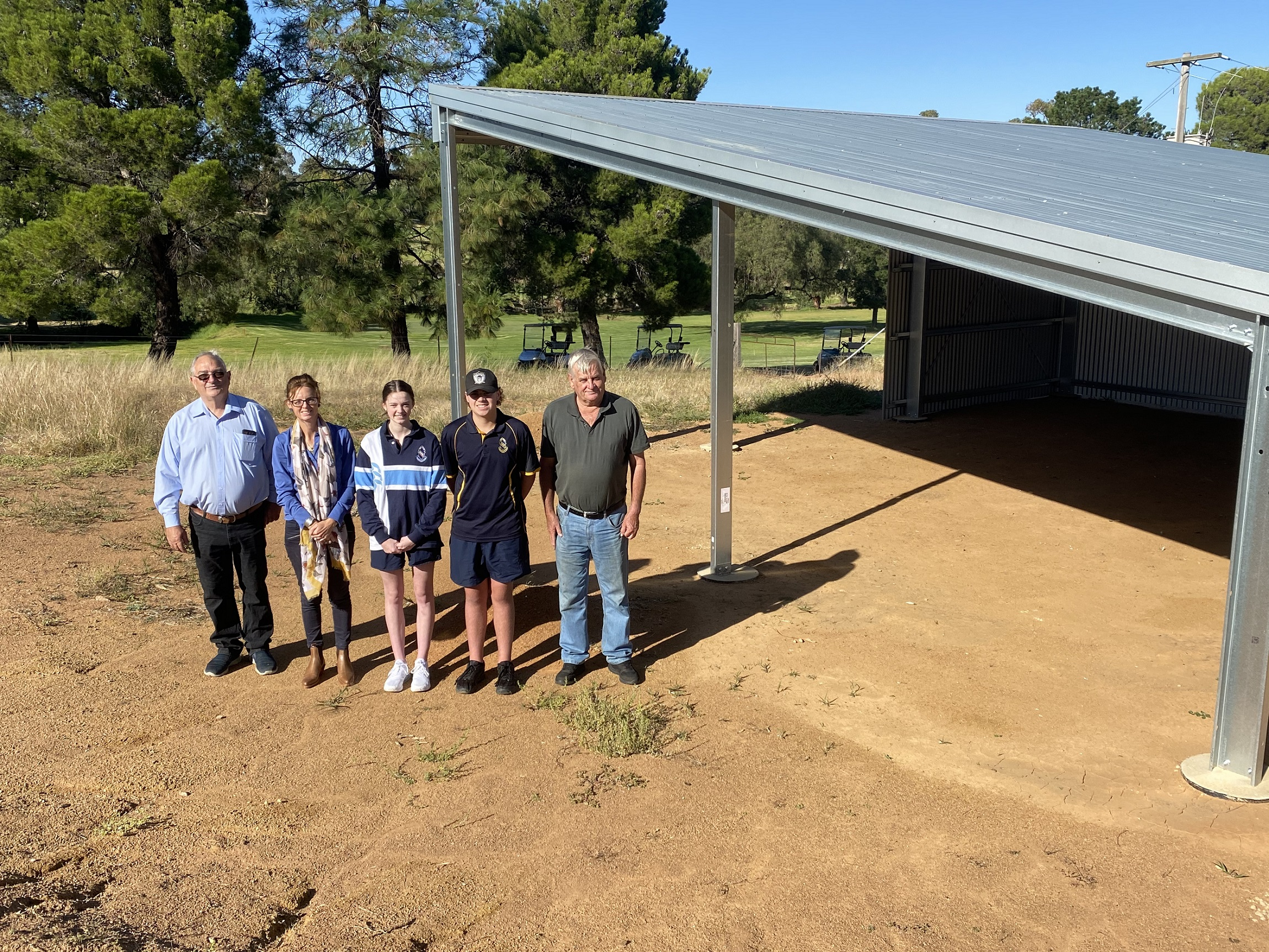 Terry Trinca, Steph Cooke MP, Bella Willis, Bailey Willis and Bruce Poole stand next to the new mid course shelter.