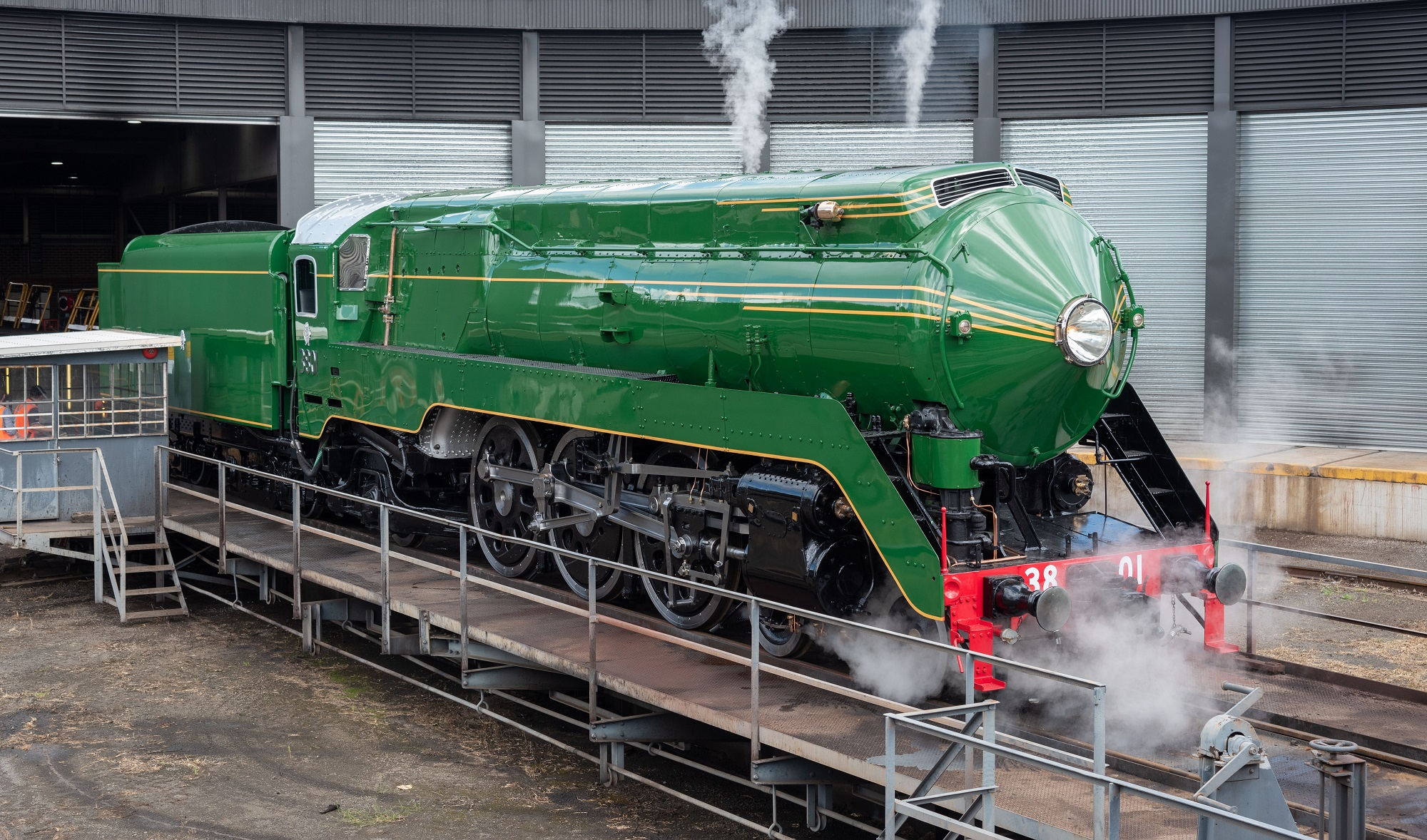 A green steam engine sits on a railway track.