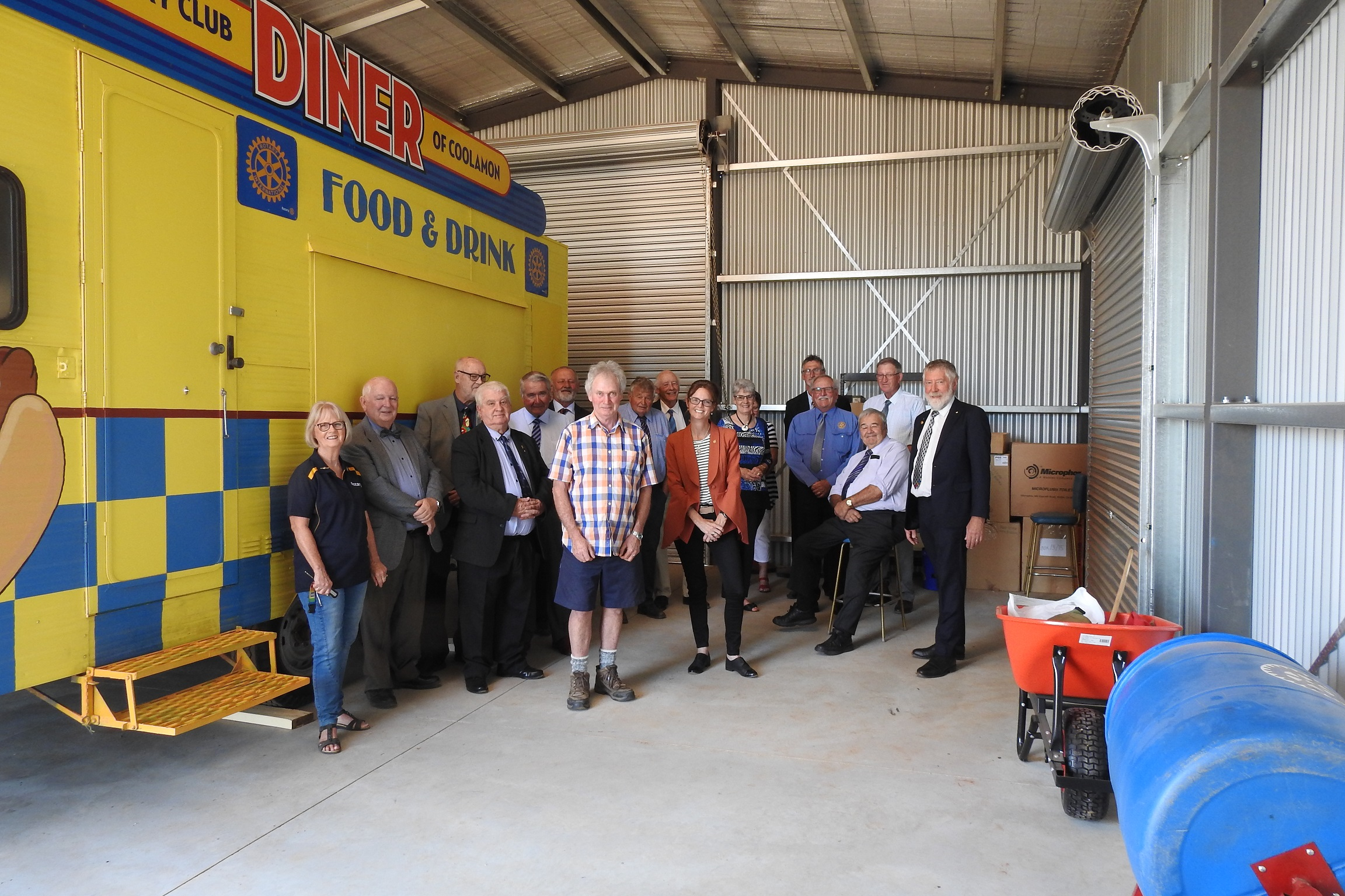 Steph Cooke and members of the Coolamon Rotary Club stand in a large shed next to a bright yellow and blue food van.