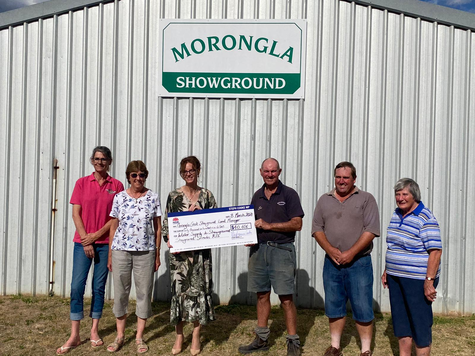Lyn Harvey, Julie Whitby, Steph Cooke MP, Graham Wallace, David Langfield and Barbara Langfield stand in front of a tin shed an hold a cheque.