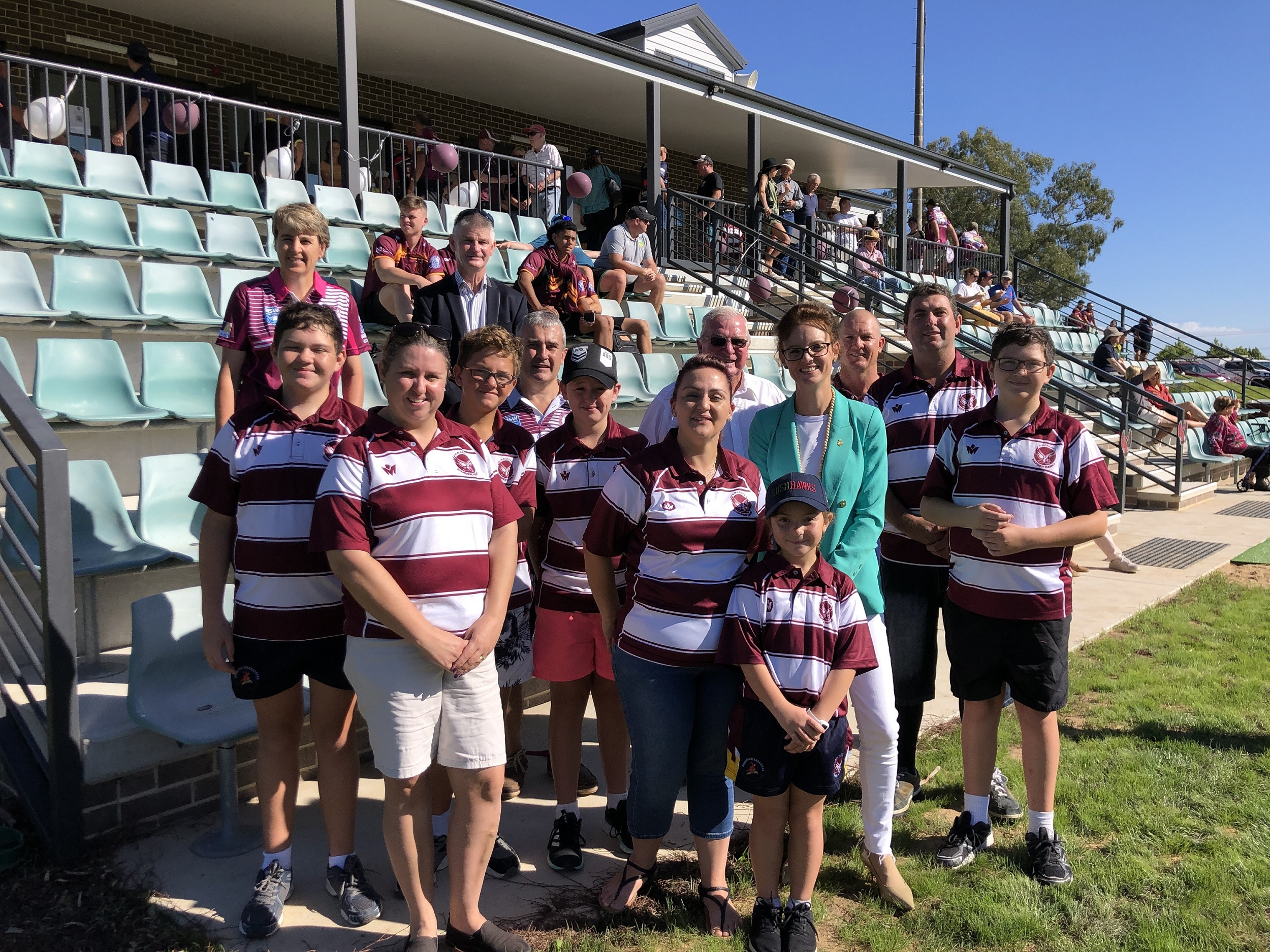 Steph Cooke stands with people in Harden football shirts in front of a green grandstand.