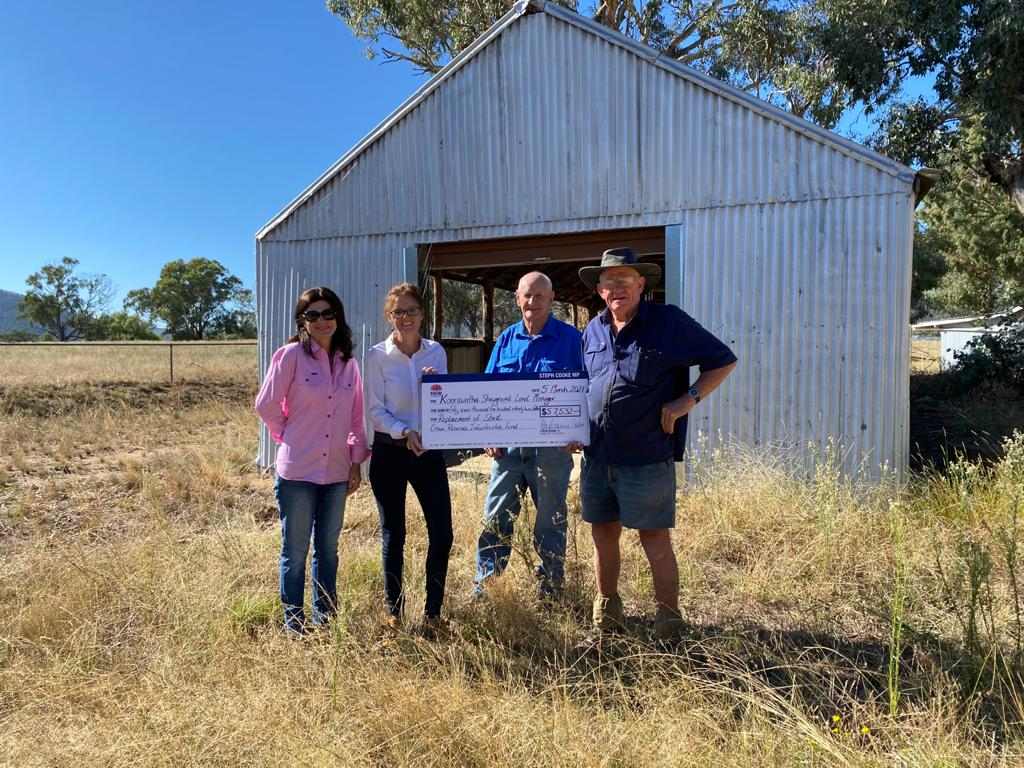 Sharon Chisholm, Steph Cooke MP, Robert Trengrove and Harry Houghton hold a large cheque and stand in front of a corrugated iron shed.
