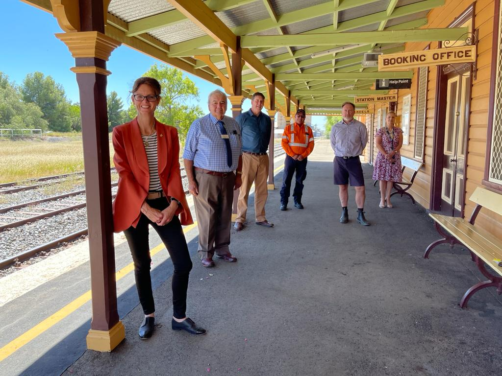Steph Cooke stands with five people on a railway platform.