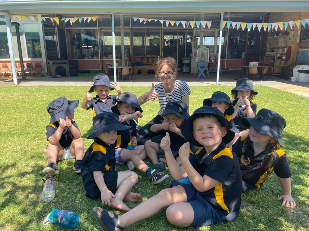 Steph Cooke sits on grass surrounded by preschool students. They all give a thumbs up and smile at the camera.