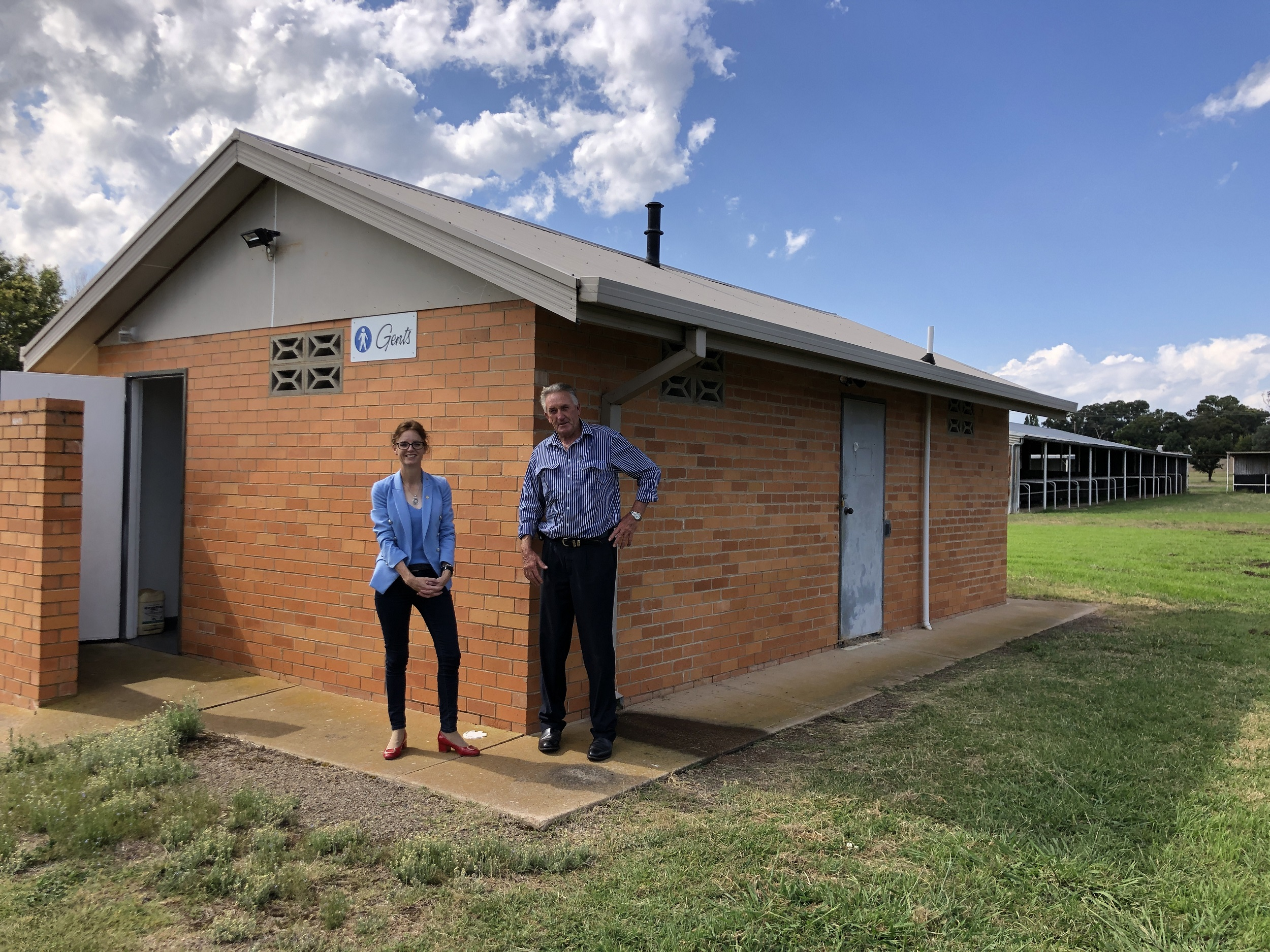 Steph Cooke and Dennis Palmer stand in front of the amenities building at the Cootamundra Showground.