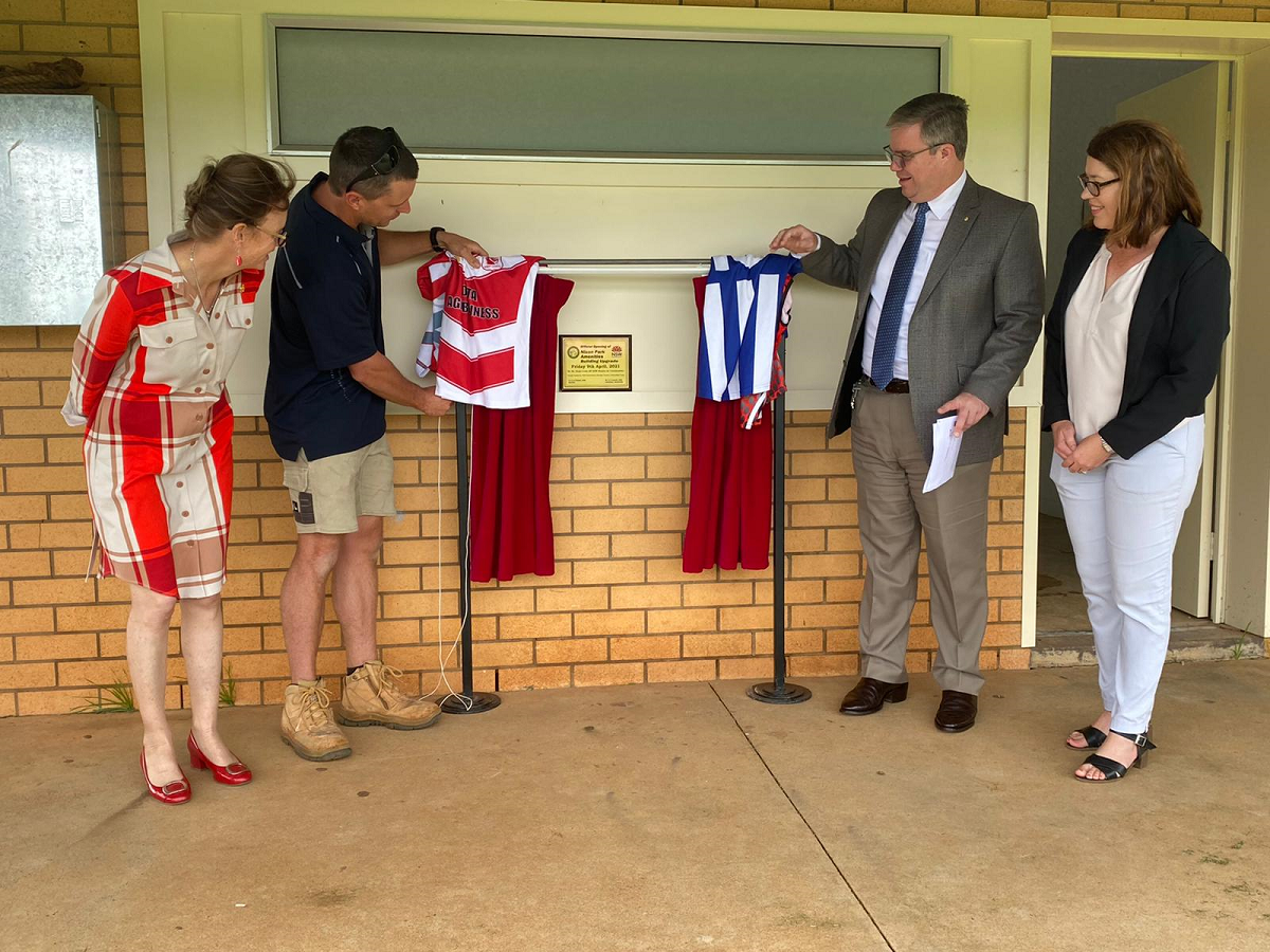 Steph Cooke MP, Grant Reed from GJR Building, Mayor Rick Firman and Clare Goulder pull apart two curtains and Temora jerseys revealing a plaque on a wall. All look and smile at the plaque.
