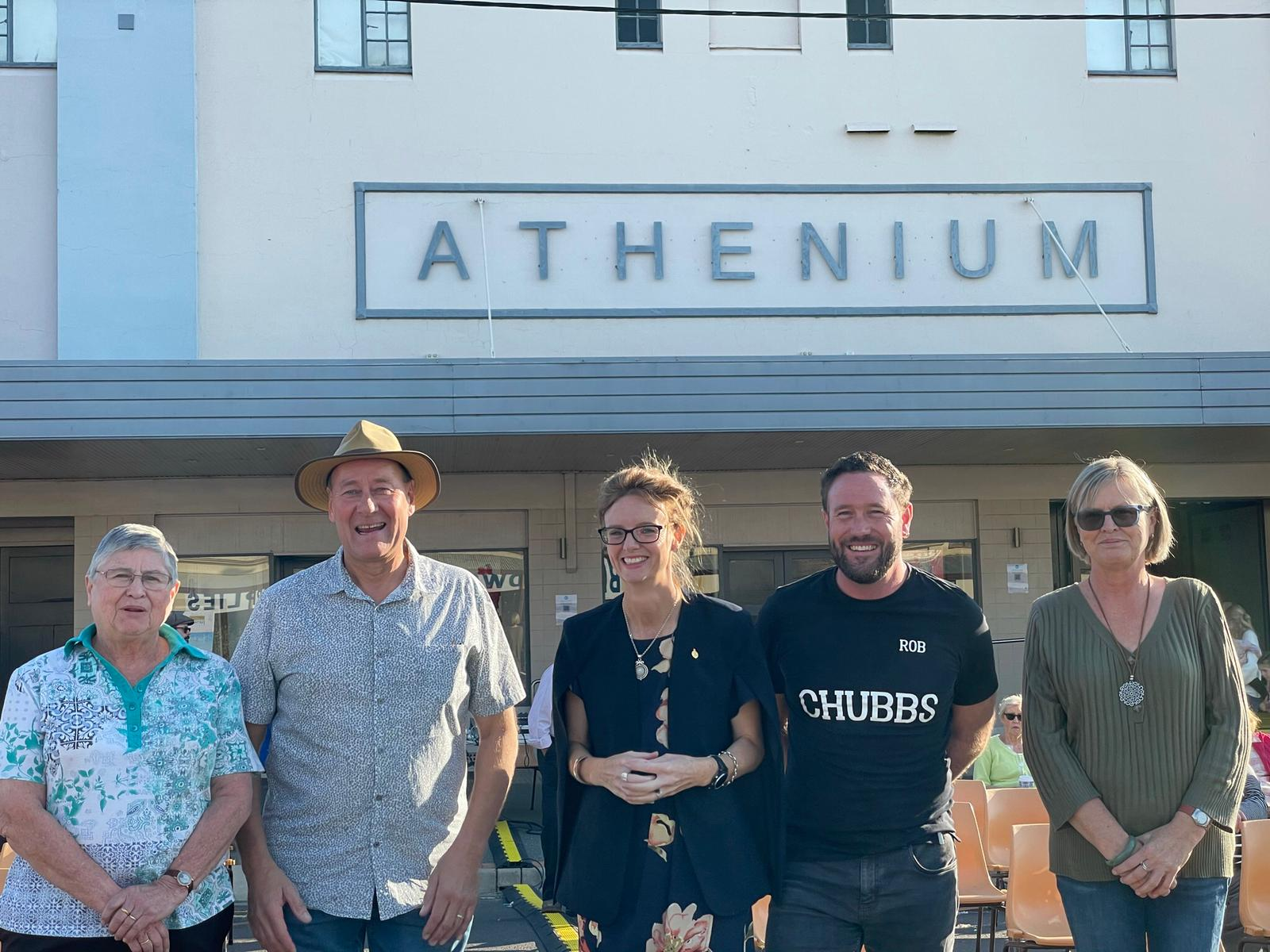 Pam Halliburton, Neil Smith, Steph Cooke and two other people smile at the camera in front of the Athenium Theatre.