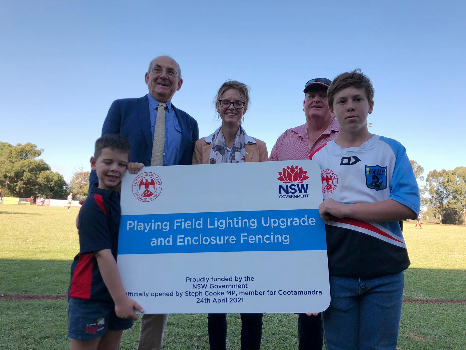 Bill West, Steph Cooke MP, Ian Robertson and two young boys hold a sign reading 'playing field lighting upgrade and enclosure fencing' with the NSW Government and Cowra Rugby Club logos.