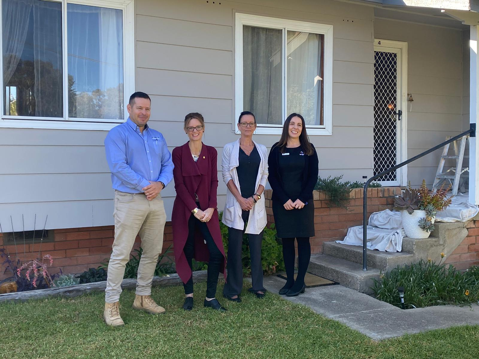 David Robertson, Steph Cooke MP, Bronwyn Weaver and Jamie Lobb stand in front of a freshly painted house and smile at the camera.