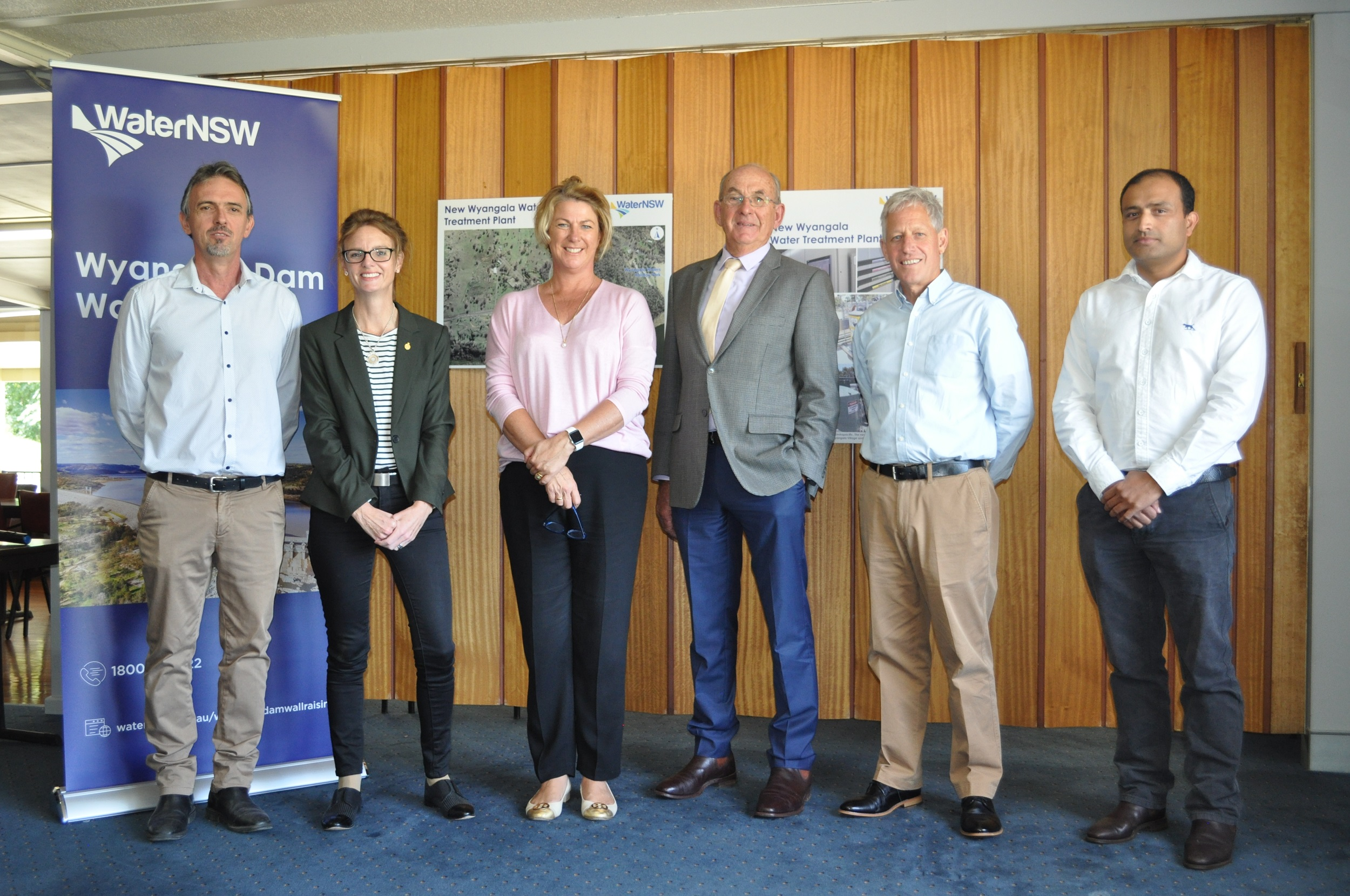 David Stanke, Steph Cooke MP, Minister Melinda Pavey, Clr Bill West, David Tucker and Sagar Adhikari stand in front of a timber wall. All smile at the camera.
