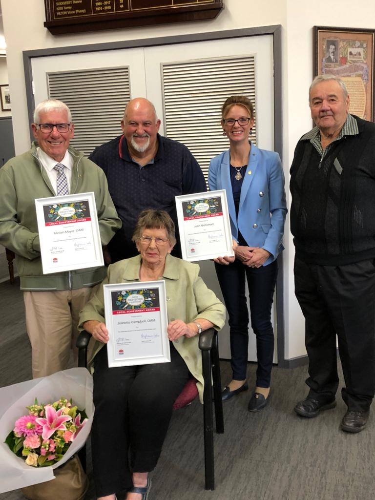 Melvyn Mayer, Jeanette Campbell, John Mohomad, Steph Cooke MP and Cr John Seymour hold certificates and are surrounded by flowers. They all smile at the camera.