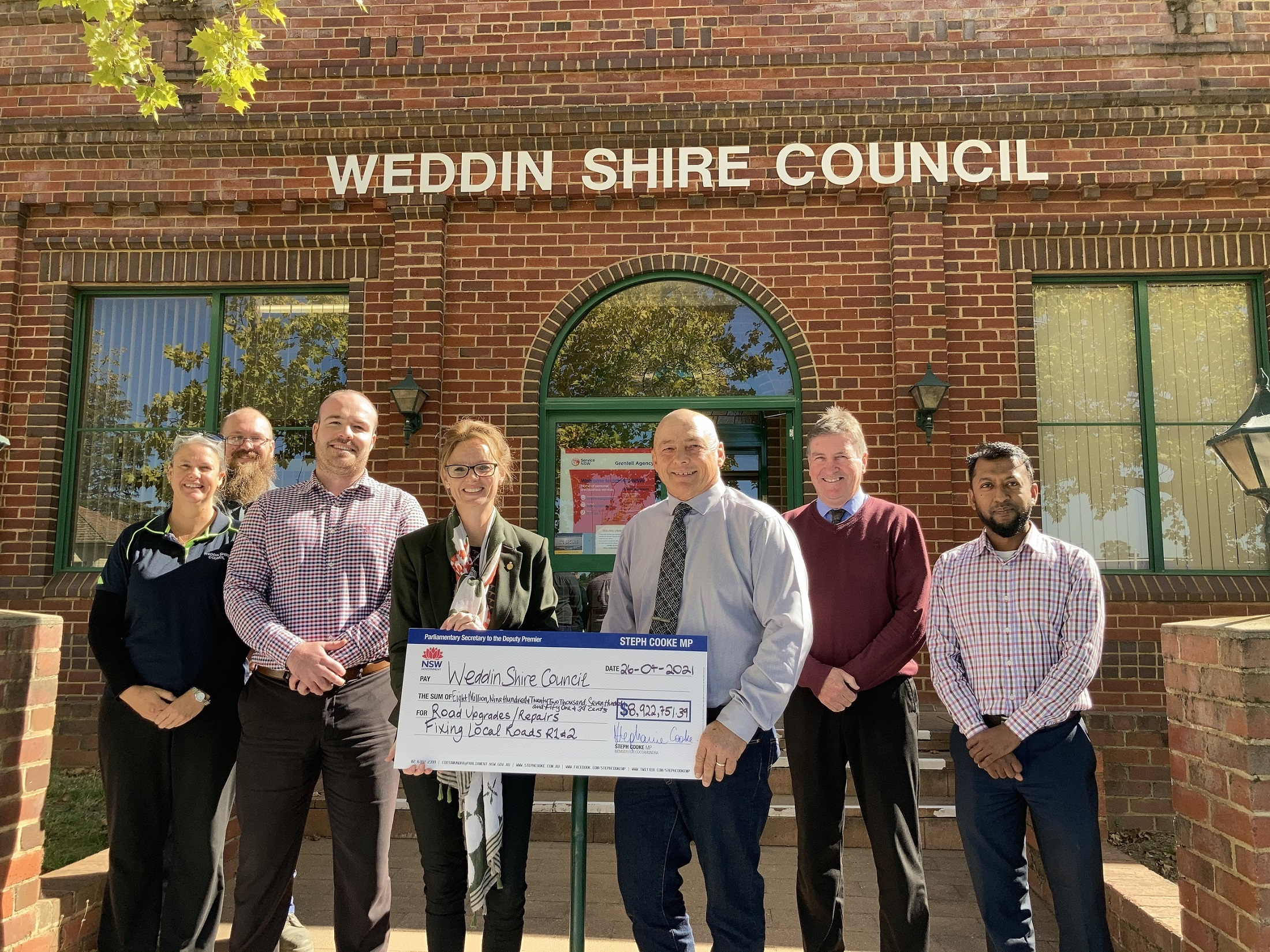 Linda Woods, Ross Garner, Jaymes Rath, Steph Cooke MP, Mark Liebich, Glenn Carroll and Raihan Rafiq hold a large cheque and stand under a sign reading 'Weddin Council Chambers'.