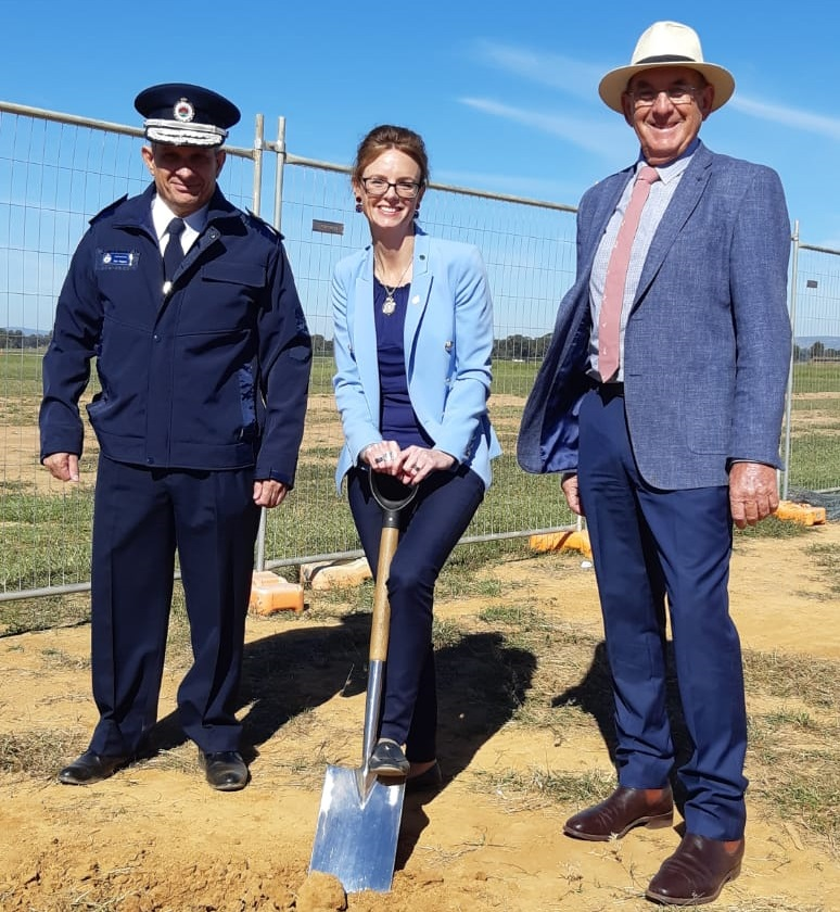 RFS Commissioner Rob Rogers stands next to Steph Cooke MP who learns on a shovel with its tip in the dirt. Cr Bill West is beside her and all three smile at the camera.
