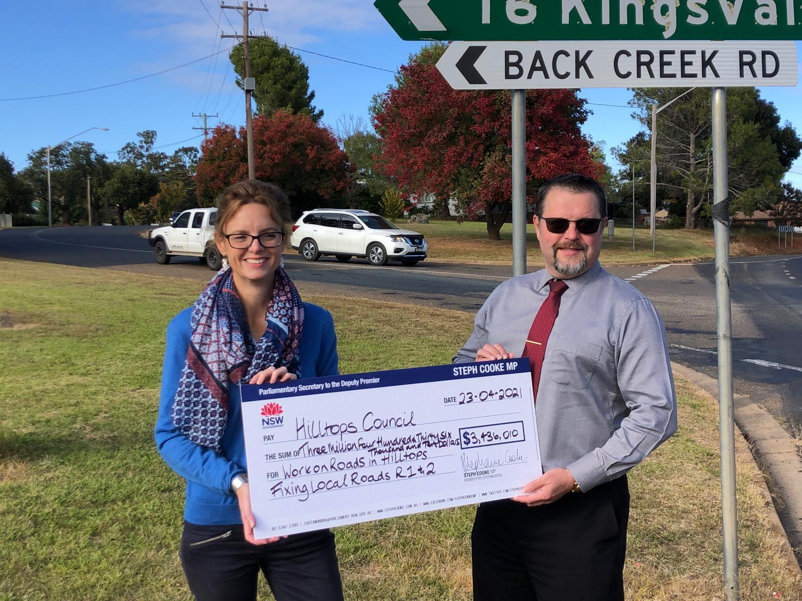 Steph Cooke MP and Anthony O'Reilly stand under a sign to Back Creek Road.