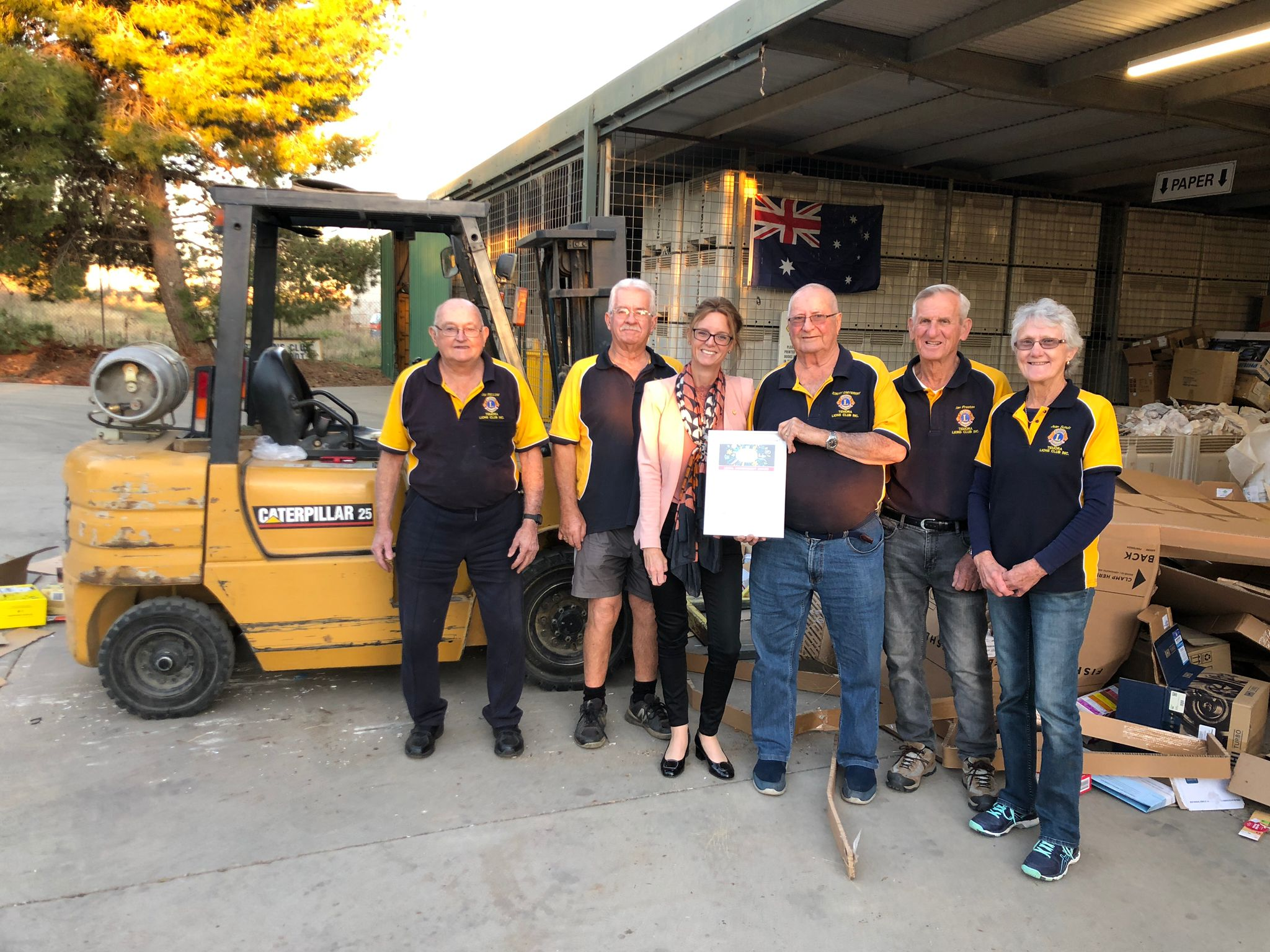 Steph Cooke stands with five Lions members who wear their yellow and navy shirts. All smile at the camera and stand in front of cardboard recycling equipment.