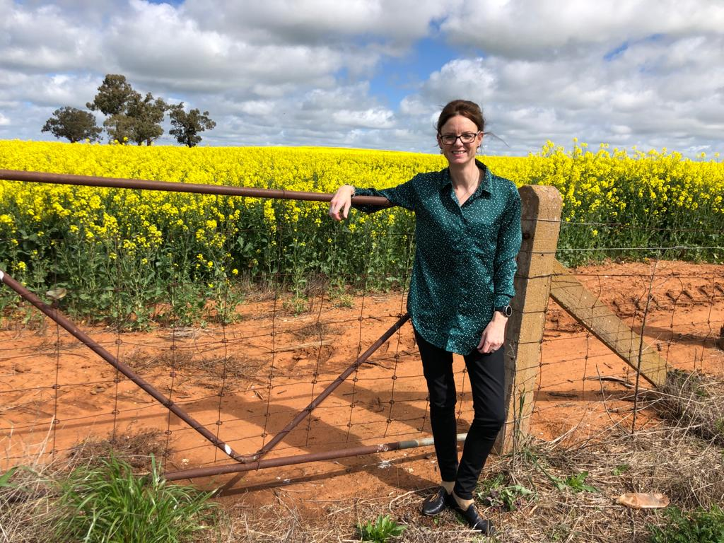 Steph Cooke leans on a farm gate in front of a canola field in full bloom.
