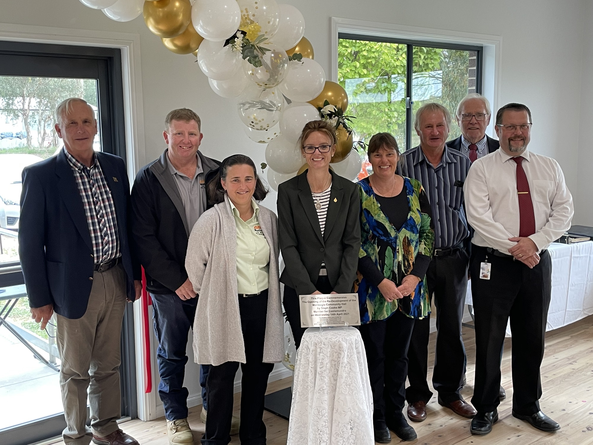 Steph Cooke stands with a group of smiling people in front of a white and golf balloon arch and behind a small silver plaque on a table.