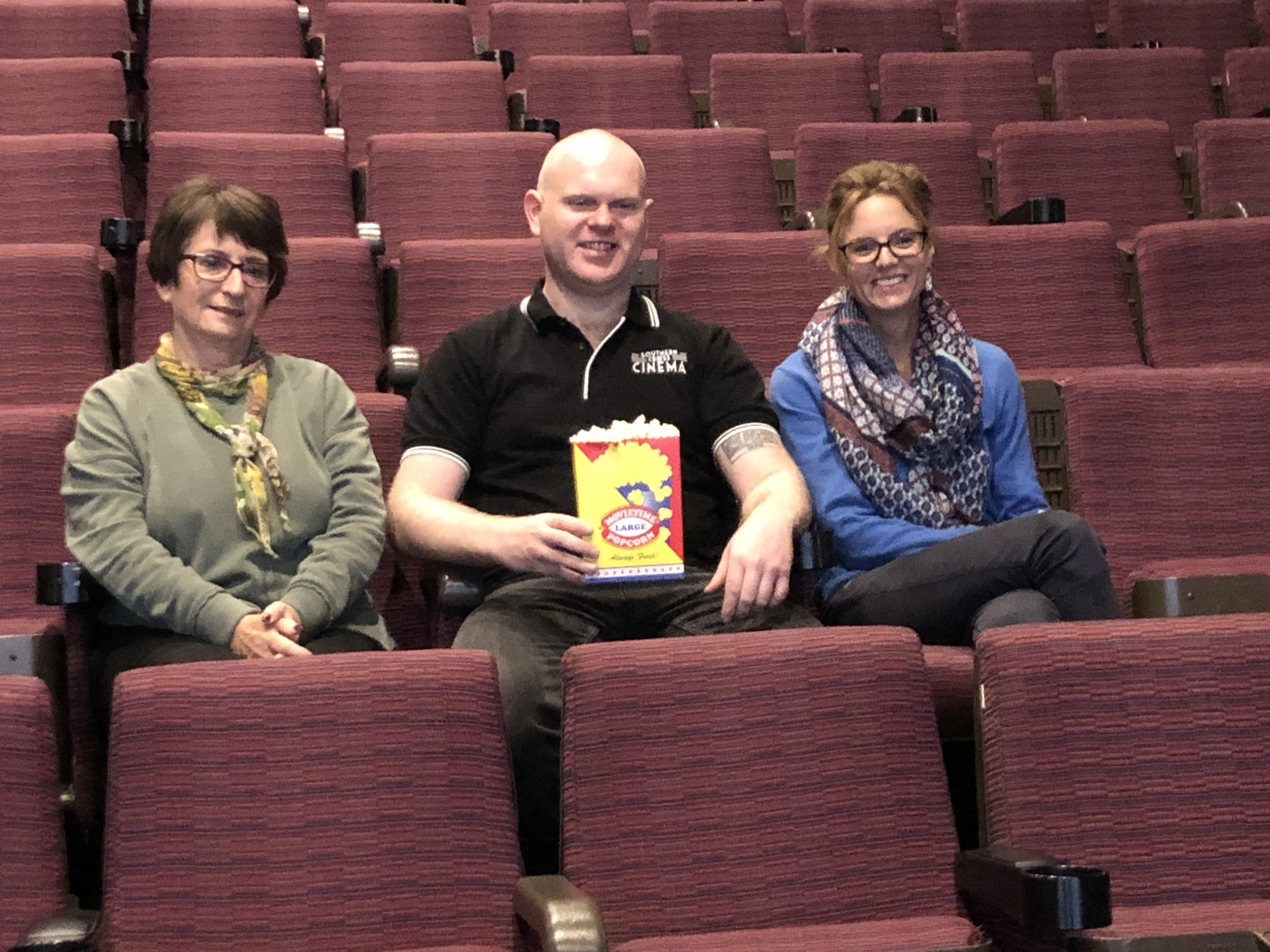 Joy Rule, Matthew Hall and Steph Cooke sit in a cinema and share a box of popcorn.