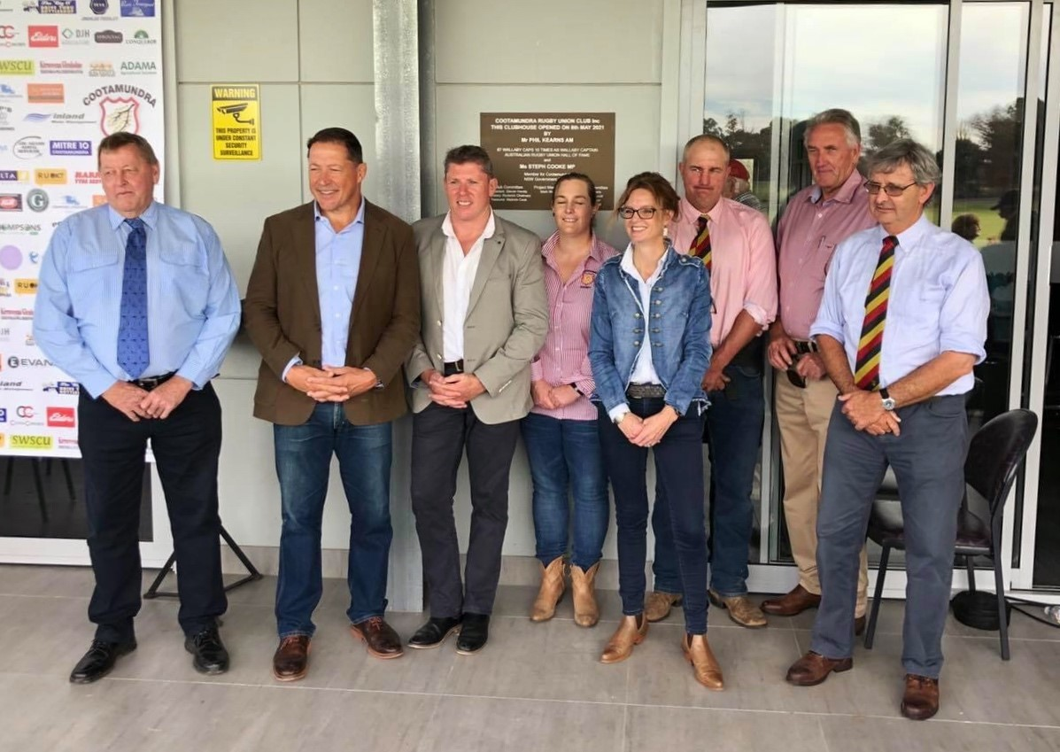 Ab Mcalister, Phil Kearns, Steph Cooke and Cowra Rugby Club representatives stand under the veranda of the new clubhouse and smile.