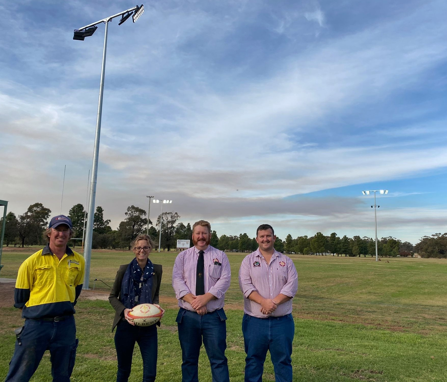 Andrew Connellan, Steph Cooke MP, Kyle Sturgess and Nick Hunt stand in front of new lighting towers at the West Wyalong Rugby Club