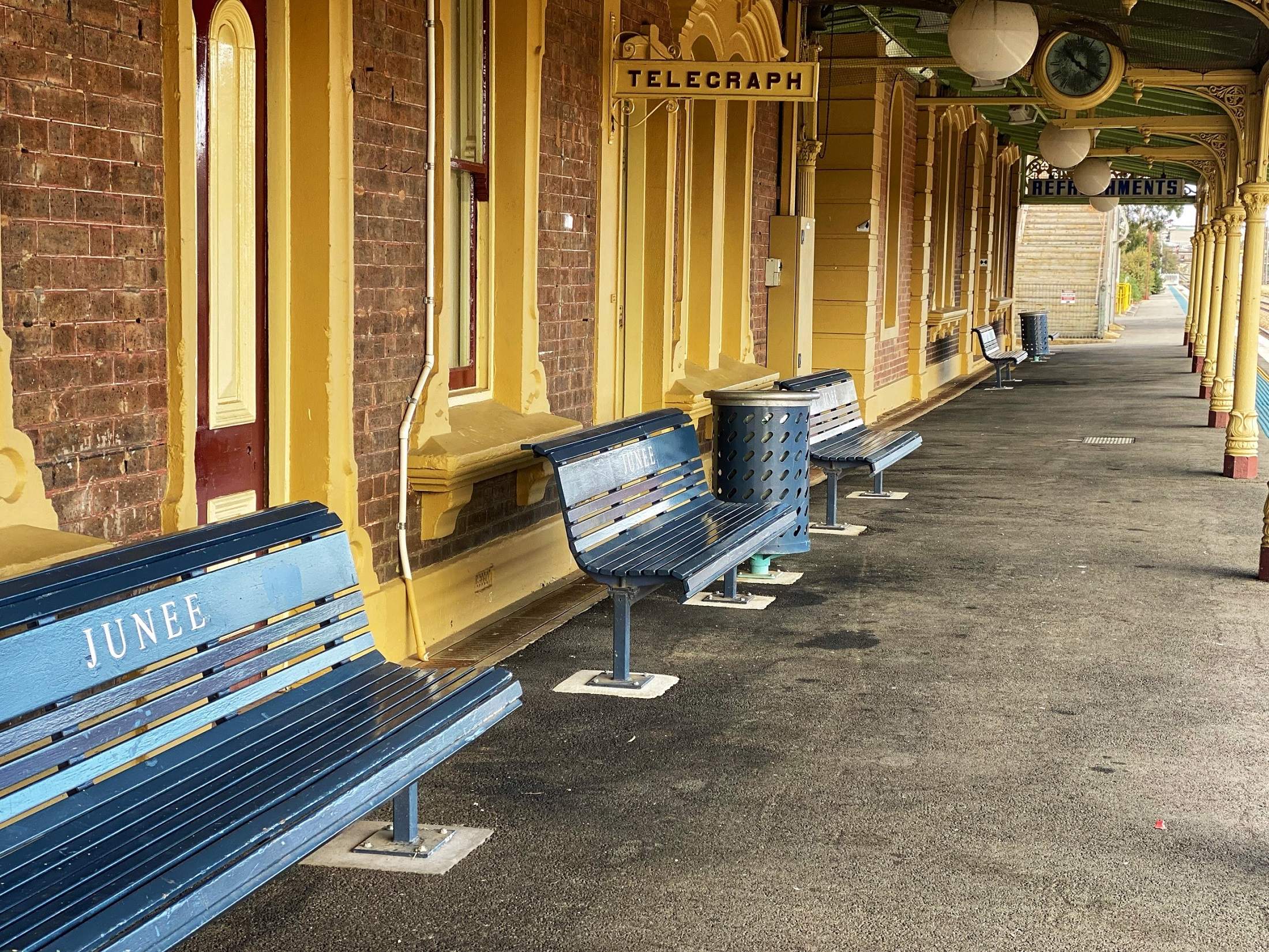Picture of the Junee rail station platform, empty blue benches can be seen in the foreground with a 'telegraph' sign hanging from the roof.