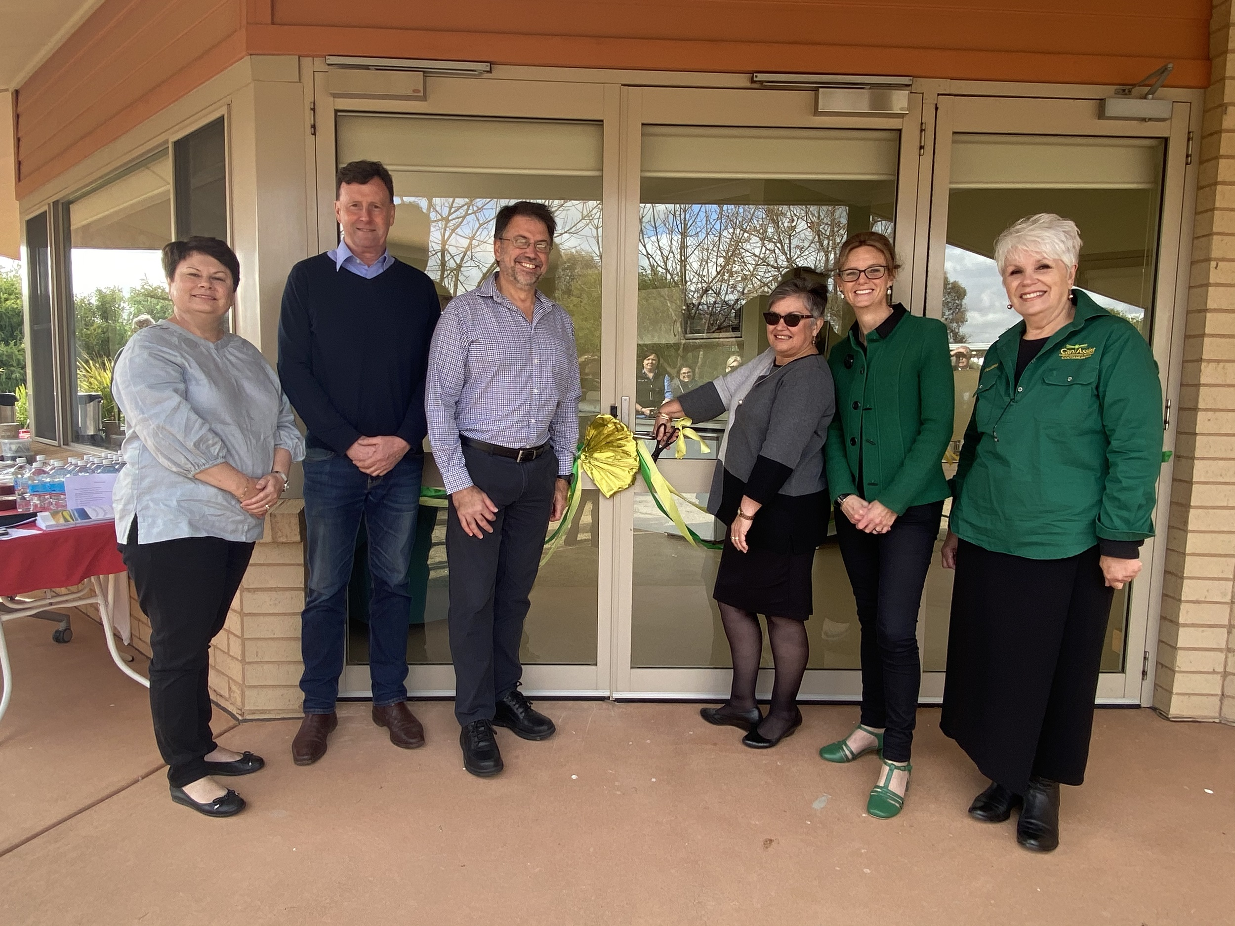 Stacey Heer, Simon Thompson, Dr Jacques Scholtz, Jennifer Apps, Steph Cooke MP and Colleen Flynn cut a green and gold ribbon on the door of the Cootamundra palliative care unit.
