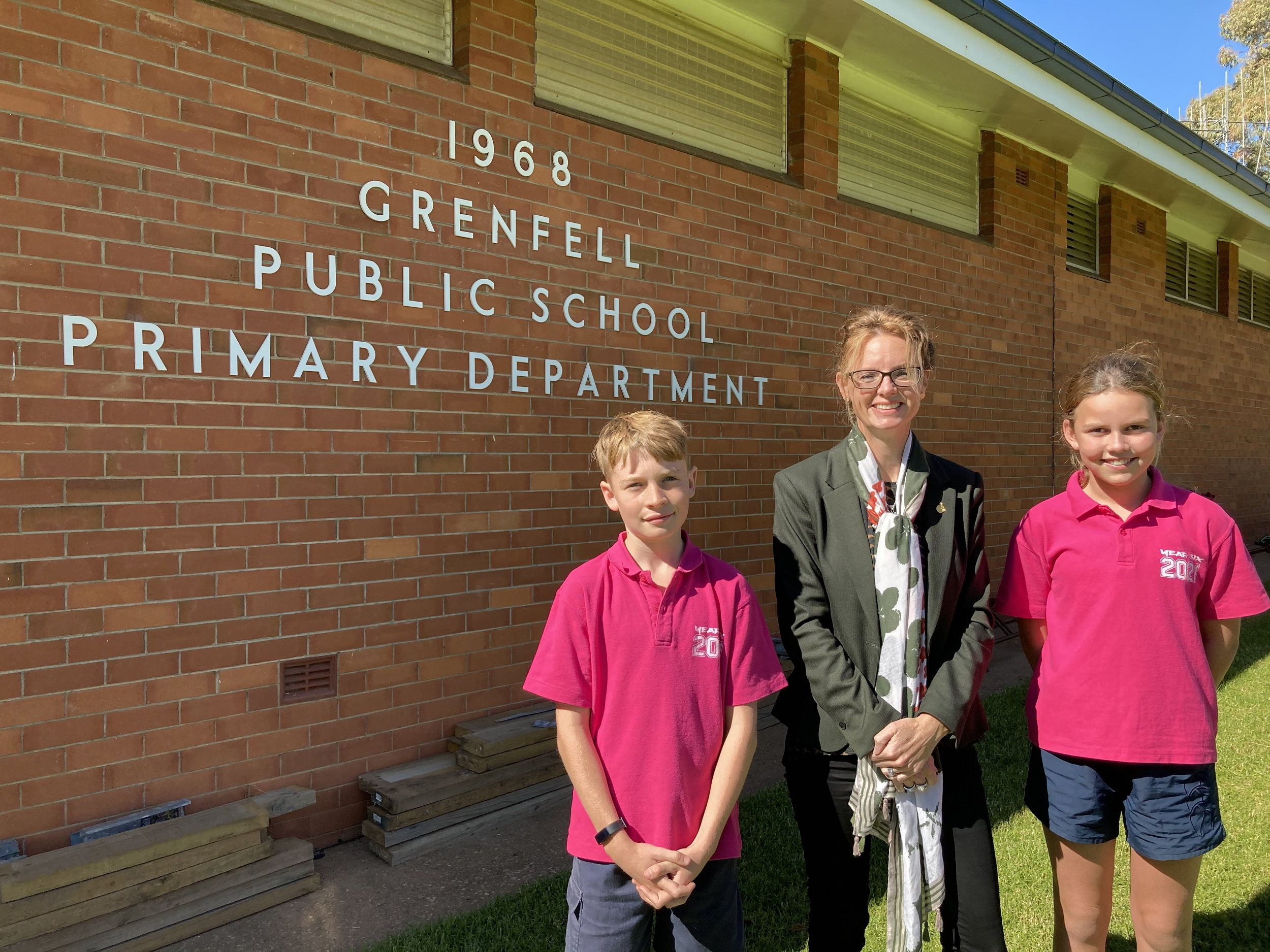 William Hedley, Steph Cooke MP wand Marley Loader stand next to a brick wall with a sign that says '1968 Grenfell Public School Primary Department'.
