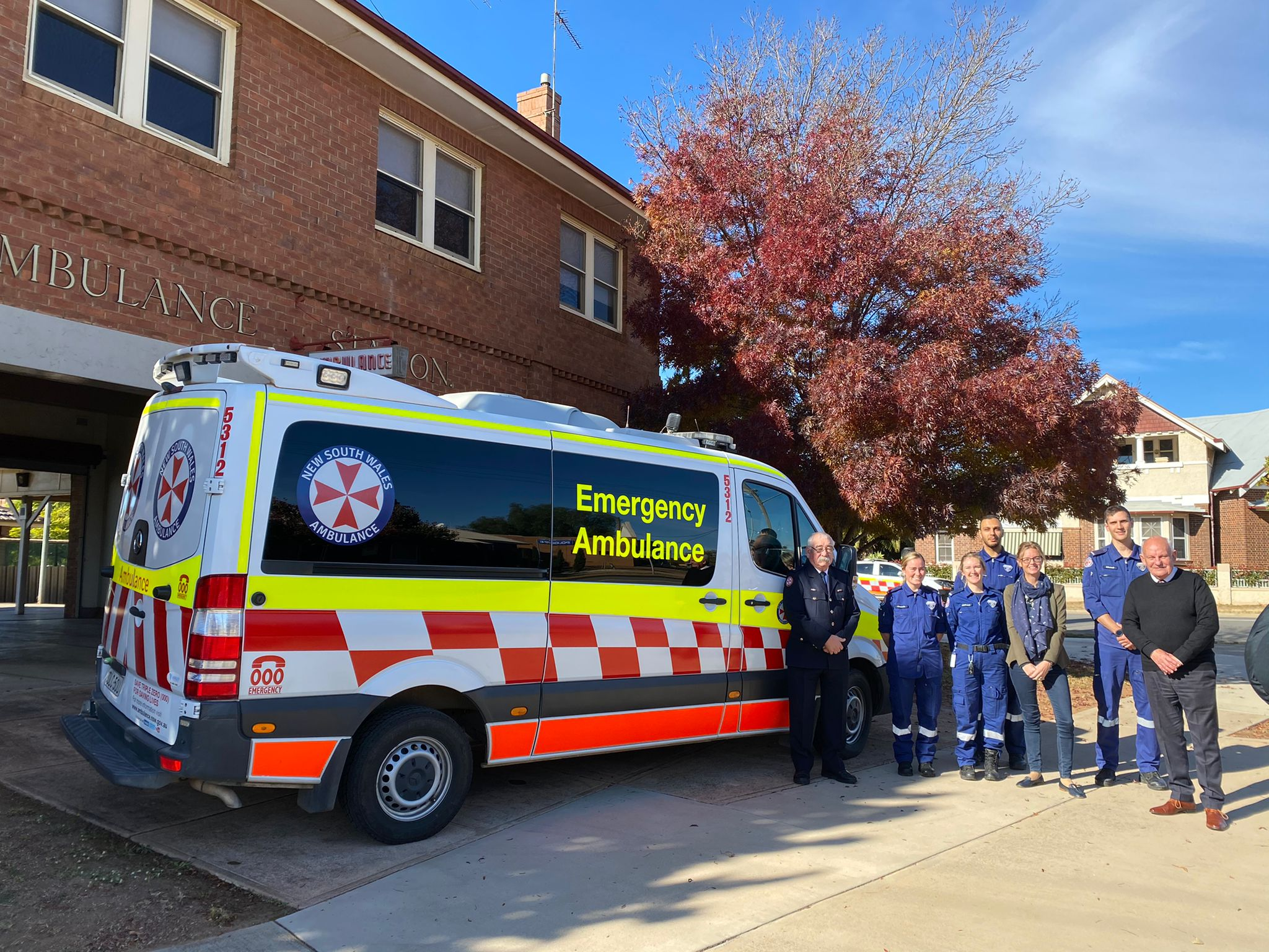 Paramedics and Steph Cooke stand in front of an ambulance.