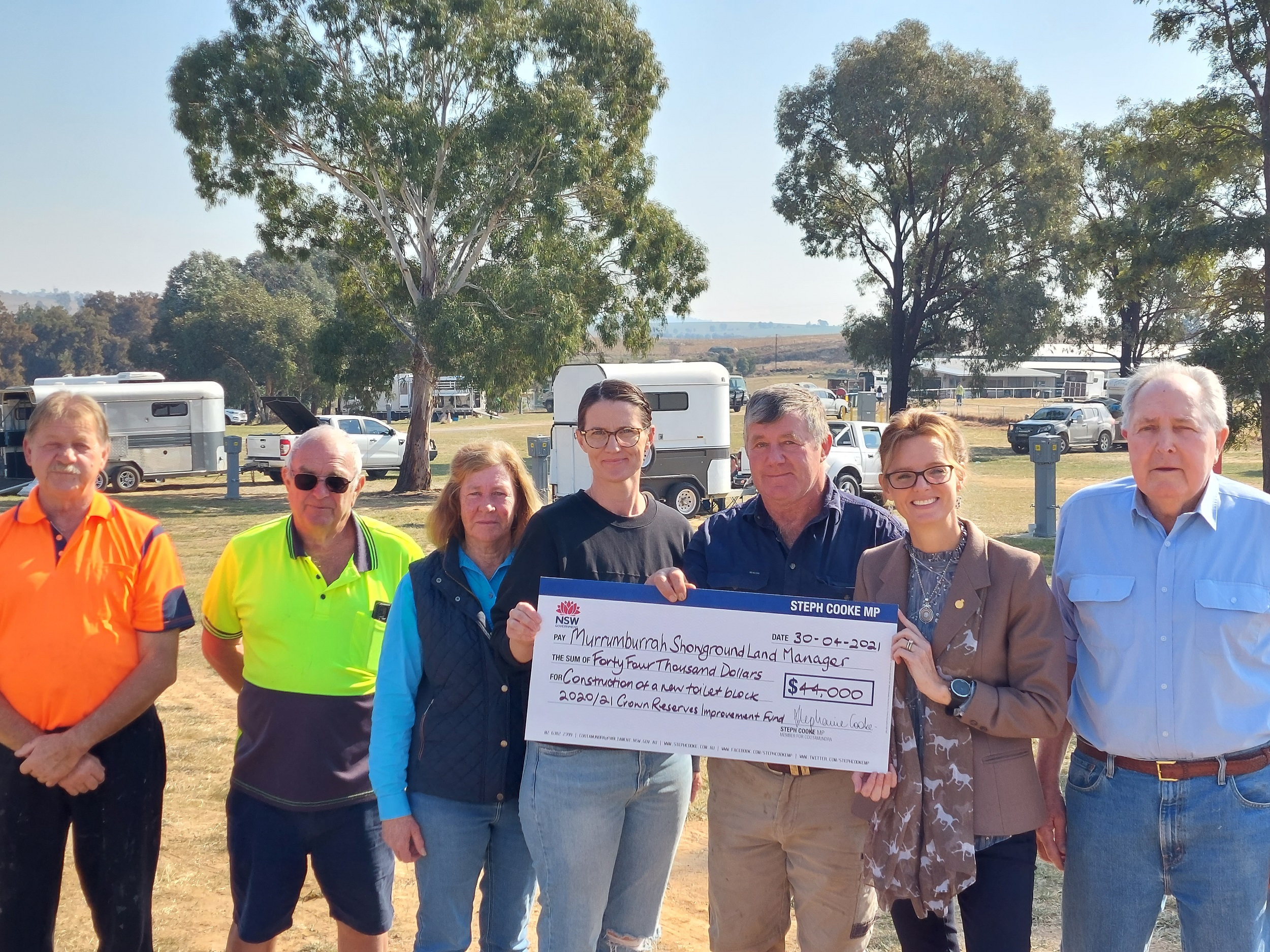 Steph Cooke and Kim Hill with the Murrumburrah Showground Land Managers. They hold a large cheque, horse floats can be seen behind them.