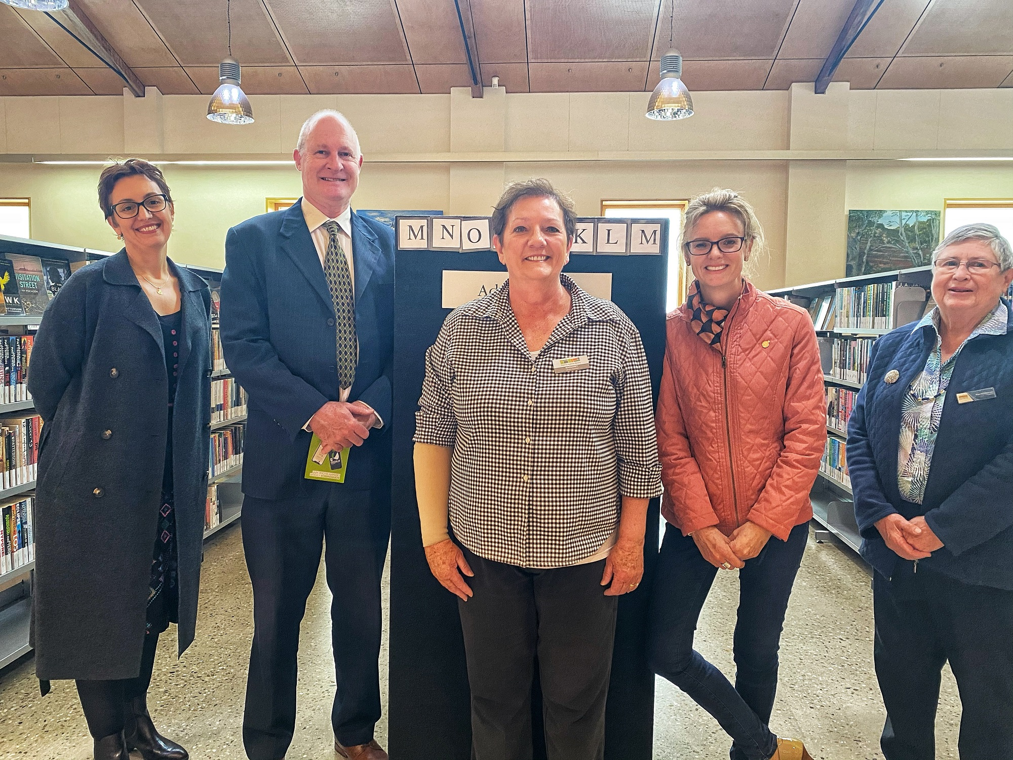 Stacey Moses, Luke Taberney, Margaret Kanaley, Steph Cooke MP and Pam Halliburton stand amongst book shelves and smile at the camera.
