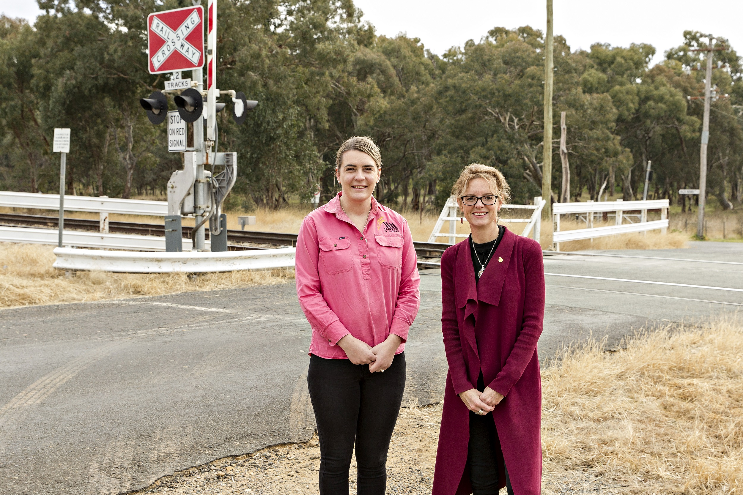 Maddie Bott and Steph Cooke stand in front of a level crossing.