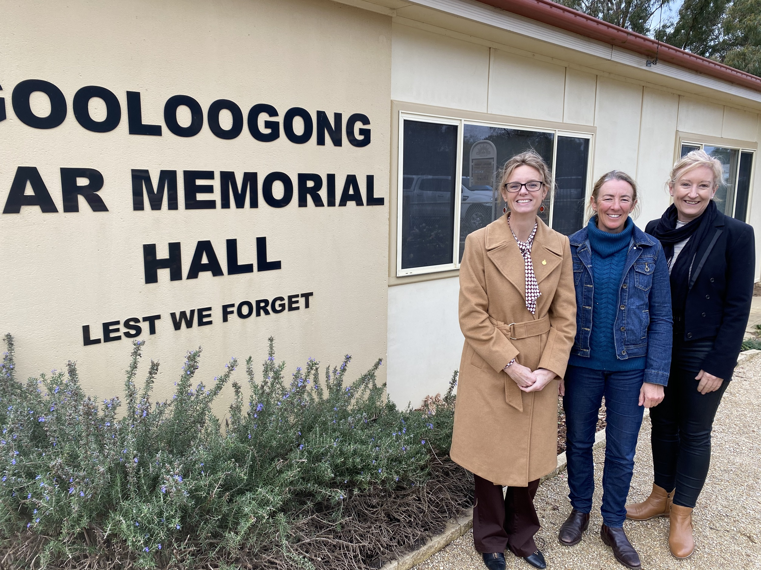 Steph Cooke MP, Kylie Reeves and Emma Marr stand in front of the Gooloogong War Memorial Hall and a sign bearing its name. All three smile at the camera