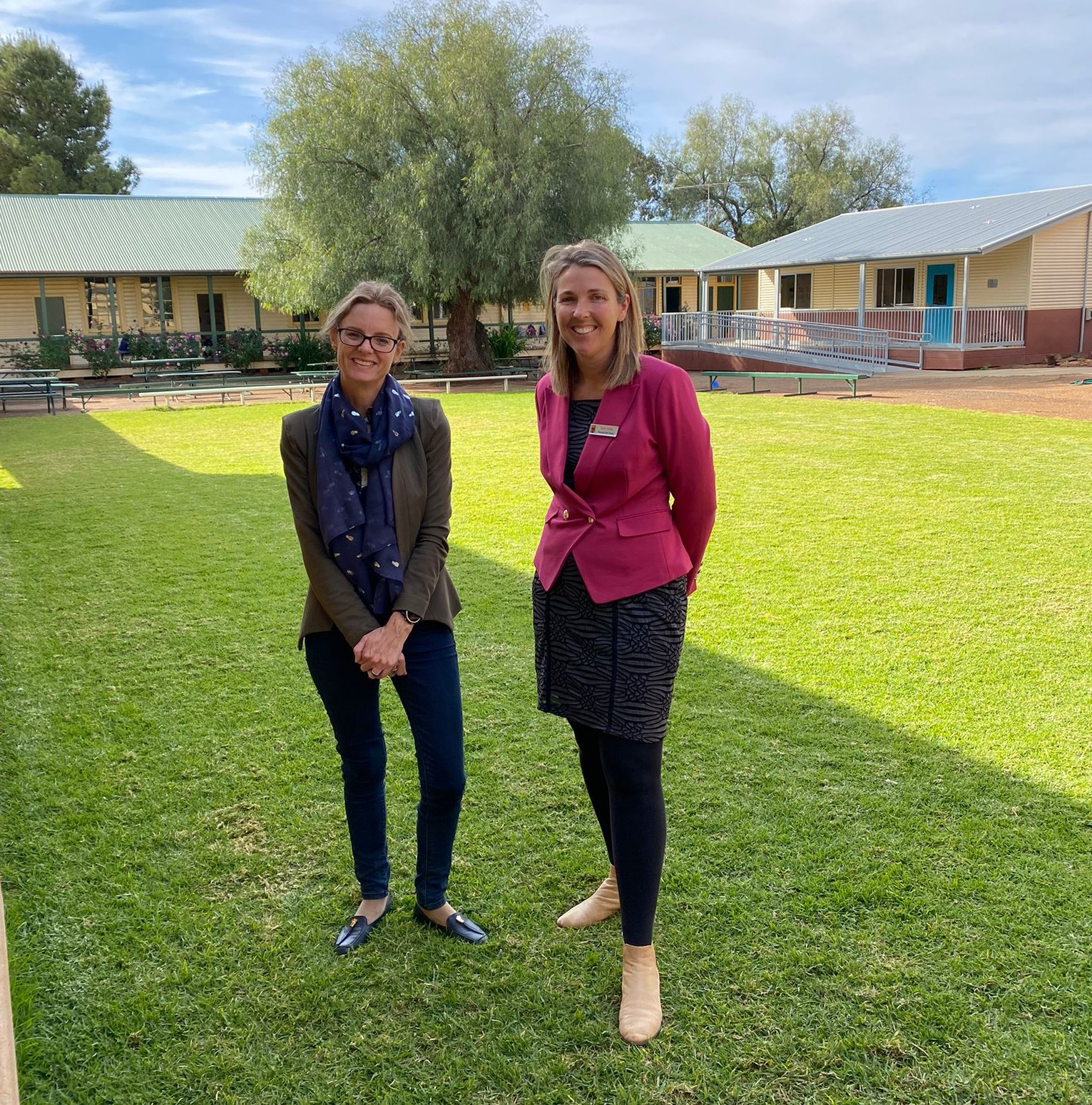 Steph Cooke and Kylie Taylor smile at the camera. Behind they classrooms can be seen.