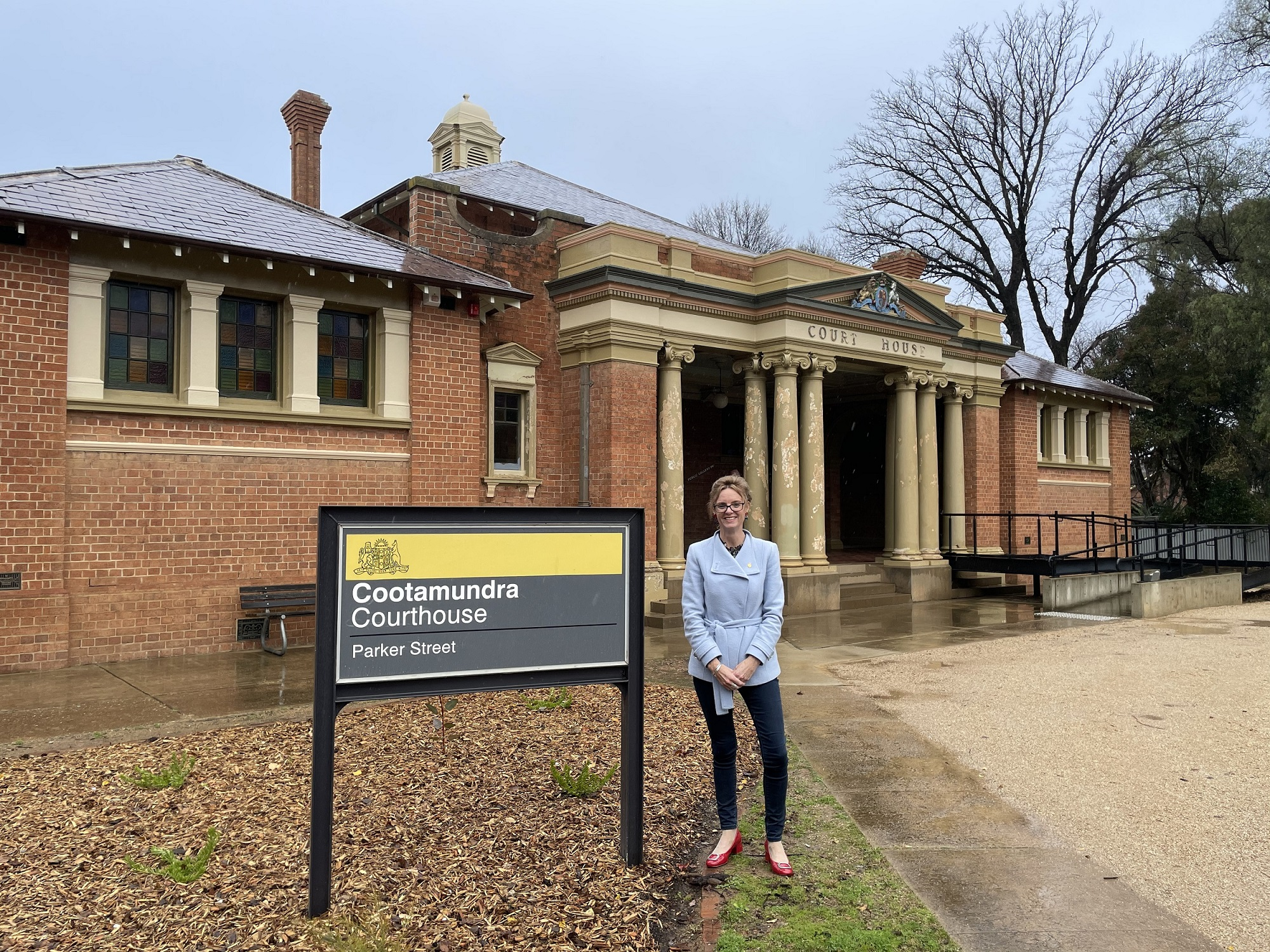 Steph Cooke stands in front of the Cootamundra Court and smiles at the camera.