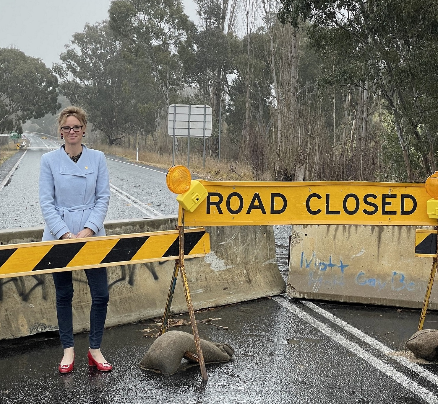 Steph Cooke stands in front of a road block and 'road closed' sign.
